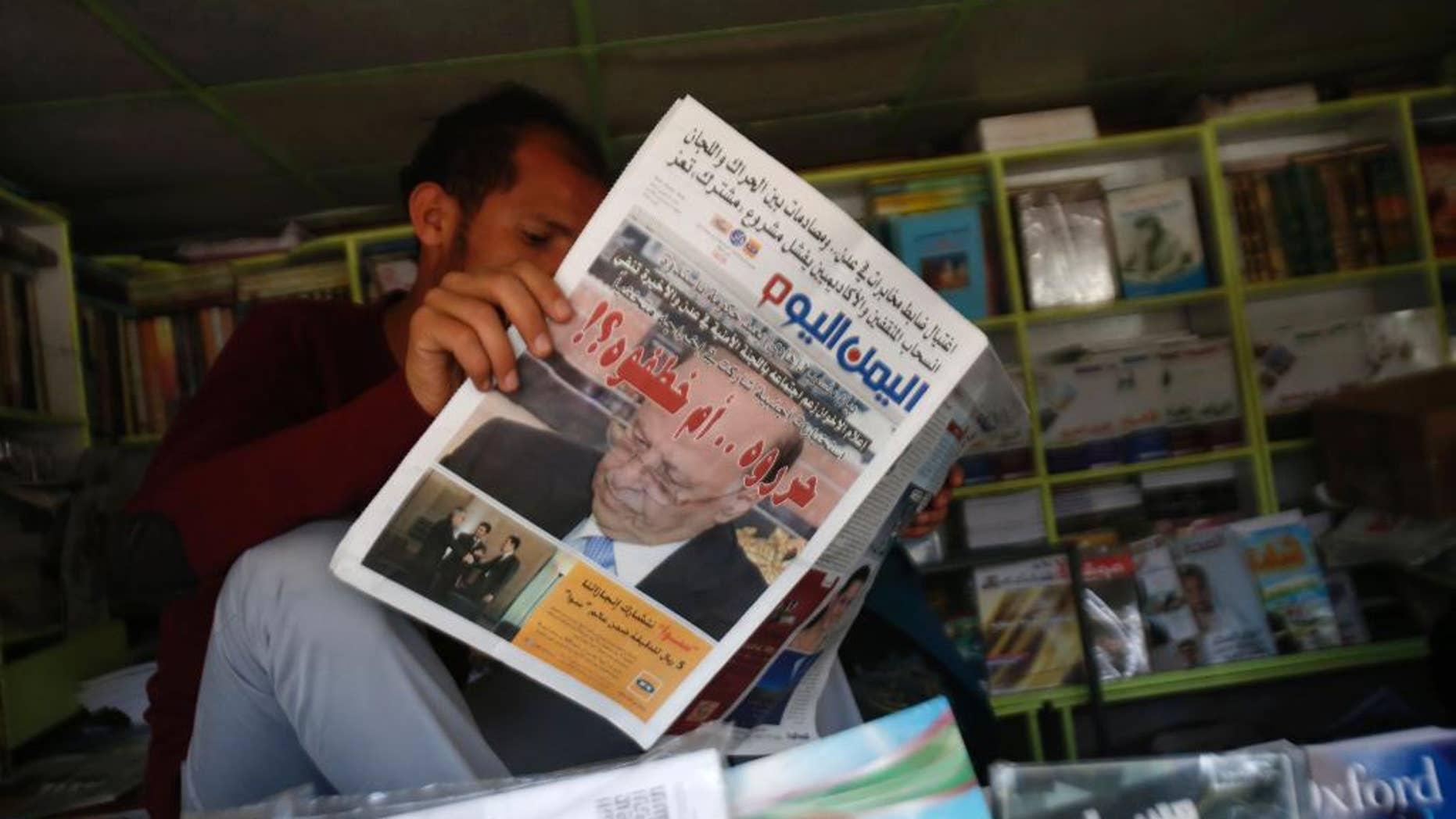 "A Yemeni man reads a newspaper featuring the front page with a photograph of former President Abed Rabbo Mansour Hadi, and a headline in Arabic that reads, "" did they release him or kidnap him?"" in Sanaa, Yemen, Sunday, Feb. 22, 2015. Virtually powerless for months, Yemen's overthrown President Hadi appeared ready to disappear from the country after fleeing Shiite rebels who held him captive in his own home. But the soft-spoken technocrat who long has avoided the limelight stepped back into it Saturday by renouncing his own resignation and challenging the Shiite Houthi rebels who hold control the capital and large parts of the country. (AP Photo/Hani Mohammed)"