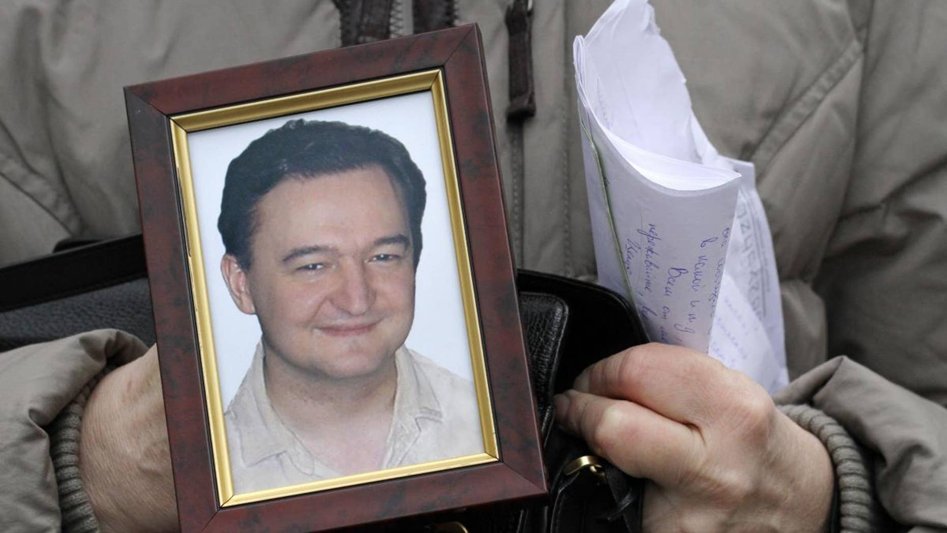Nataliya Magnitskaya, mother of lawyer Sergei Magnitsky who died in jail two weeks ago, holds a portrait of him and letters he sent to her from jail, as she speaks in central Moscow, Russia, Nov. 30, 2009 (AP)