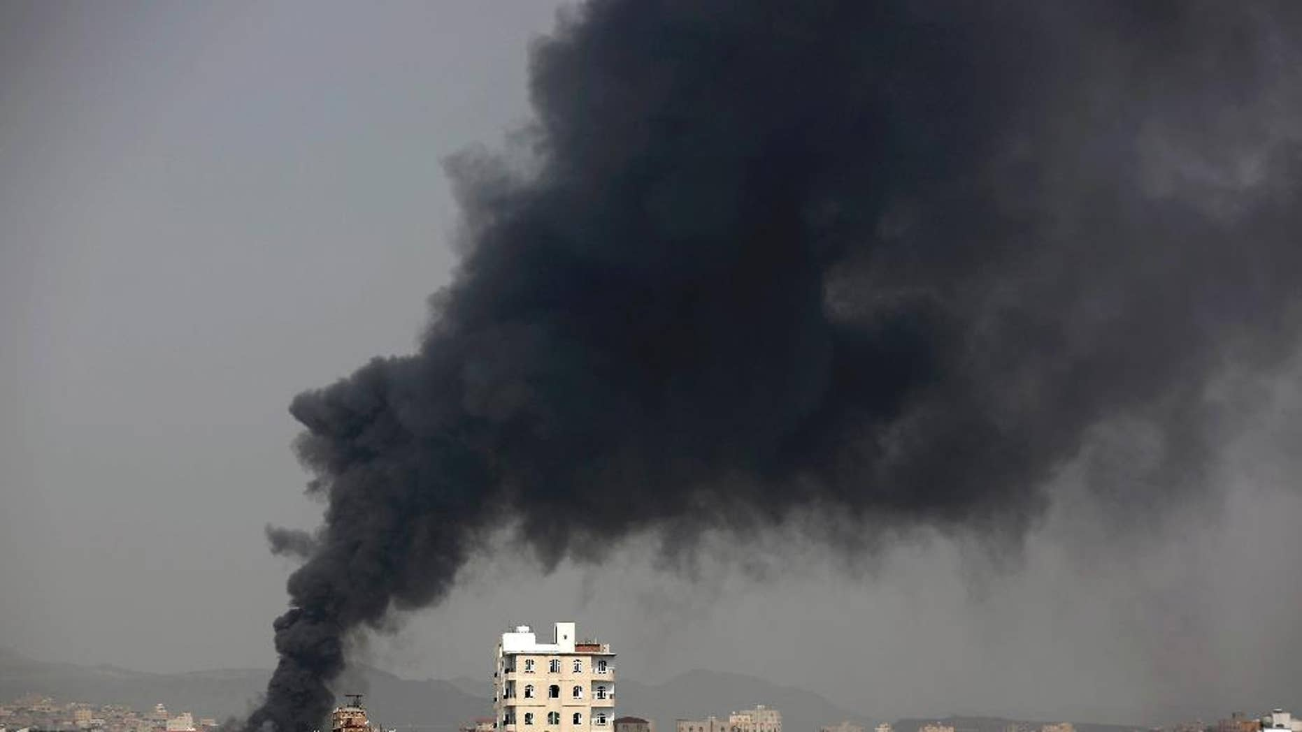 In this Aug. 9, 2016 photo, smoke rises after Saudi-led airstrikes hit a food factory in Sanaa, Yemen. In the air campaign by Saudi Arabia and its allies against Yemen's Shiite rebels, rights experts say there has been a pattern by the Saudi-led coalition in depending on faulty intelligence, failing to distinguish between civilian and military targets and disregarding the likelihood of civilian casualties. Experts say some of the strikes likely amount to war crimes. (AP Photo/Hani Mohammed)