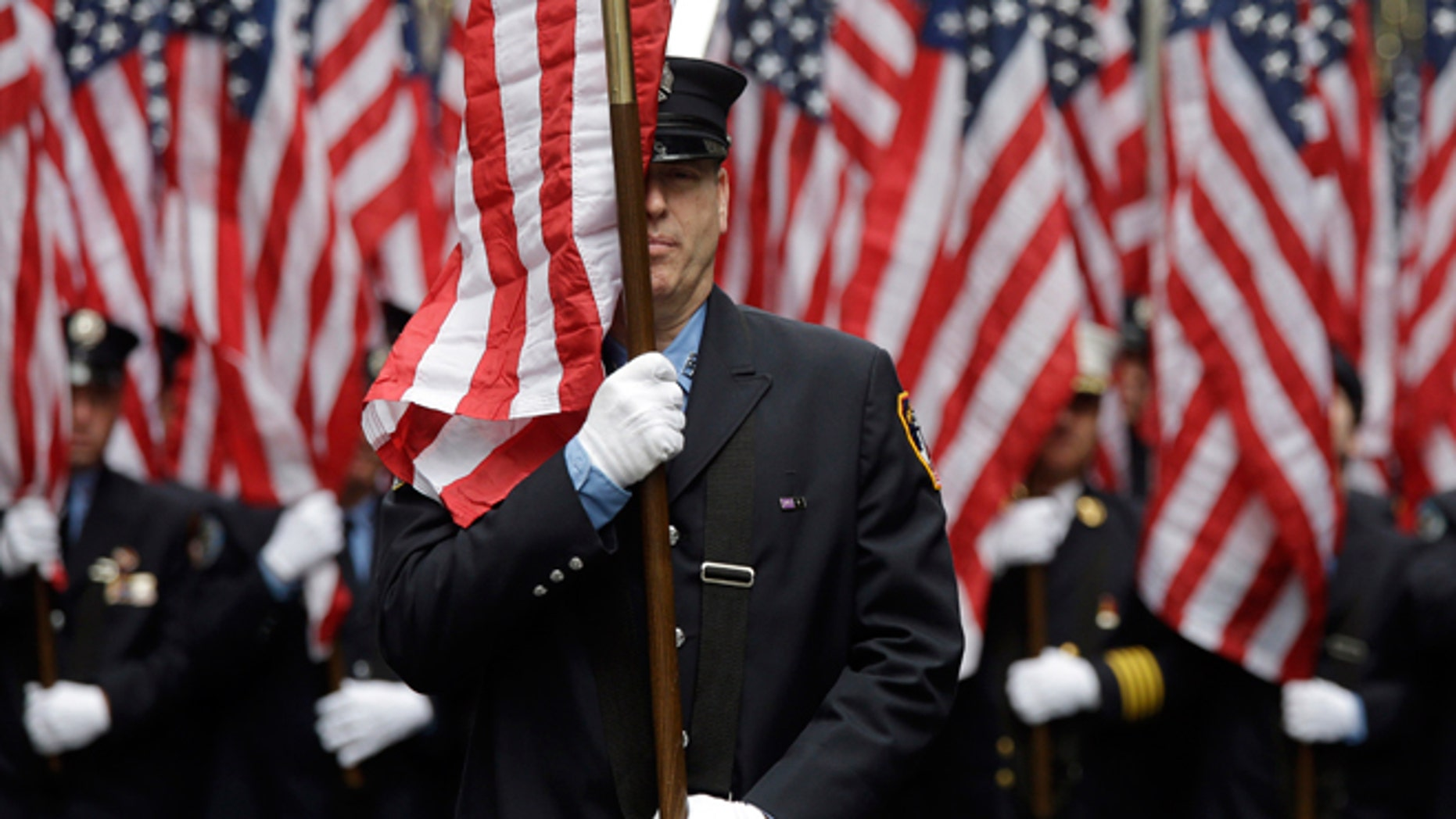 FILE -- March 17, 2015: Firefighters carrying 343 American flags representing each of their colleagues who died during the terrorist attacks on the World Trade Center, march up Fifth Ave. during the St. Patrick's Day Parade.