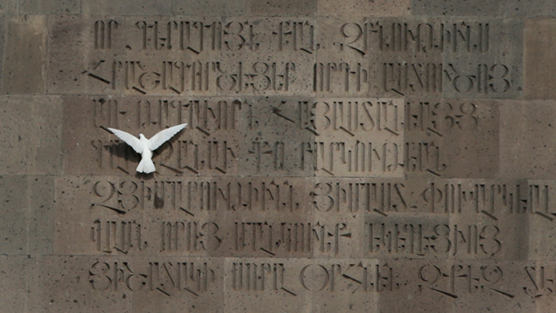 April 23, 2015: A dove tries to sit on a monument wall in Echmiadzin, the religious center of the Armenian Church outside the Armenian capital, Yerevan.