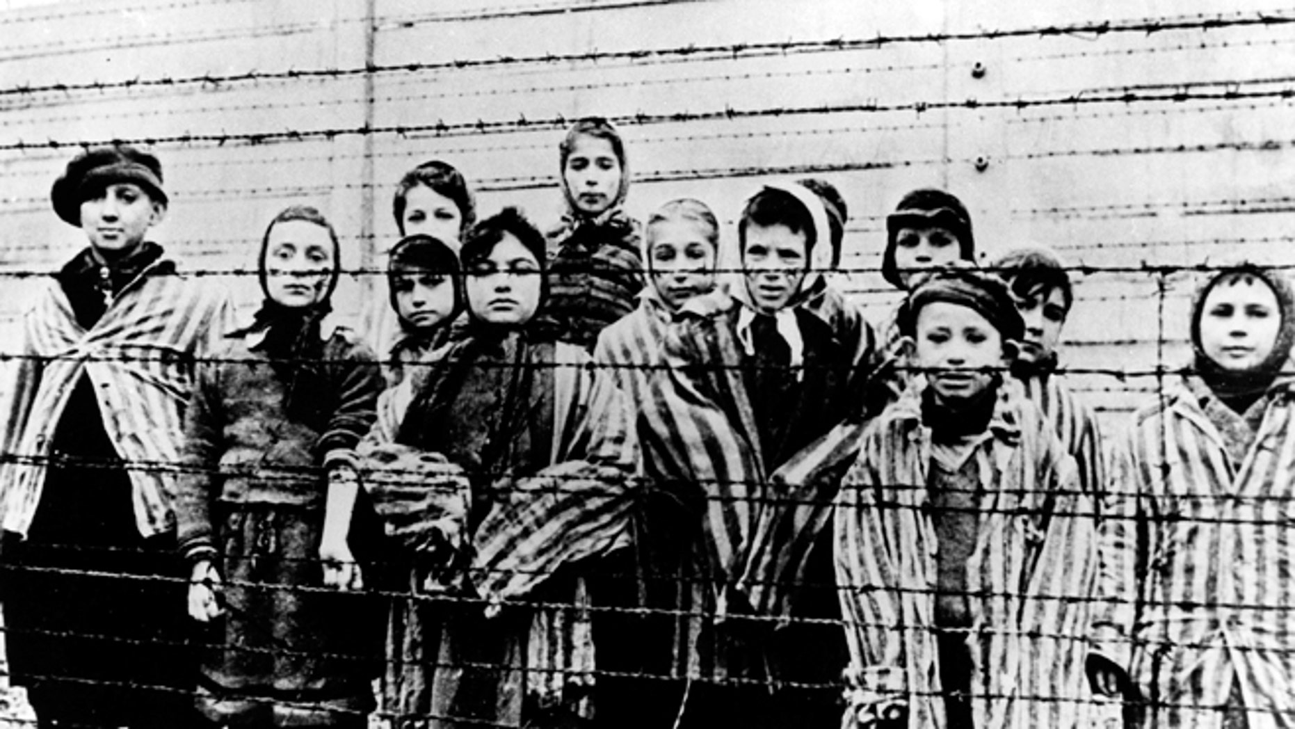 FILE - A picture taken just after the liberation by the Soviet army in January, 1945, shows a group of children wearing concentration camp uniforms behind barbed wire fencing in the Auschwitz Nazi concentration camp. (AP)