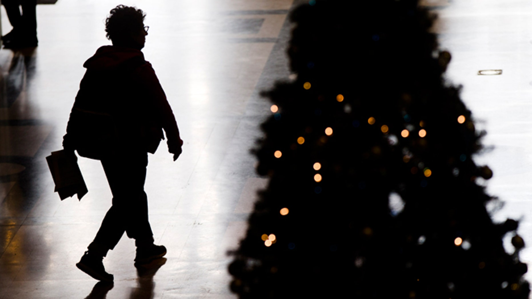 FILE -- Dec. 17, 2014: A visitor to the Free Library of Philadelphia walks through the lobby by a Christmas tree in Philadelphia.