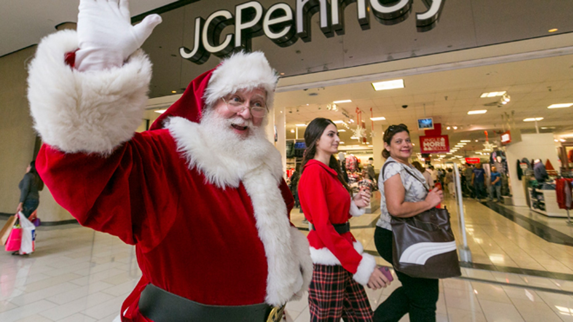 FILE -- Nov. 28, 2014: A man dressed as Santa Claus greets shoppers outside the J.C. Penney store at the Glendale Galleria shopping mall in Glendale, Calif.