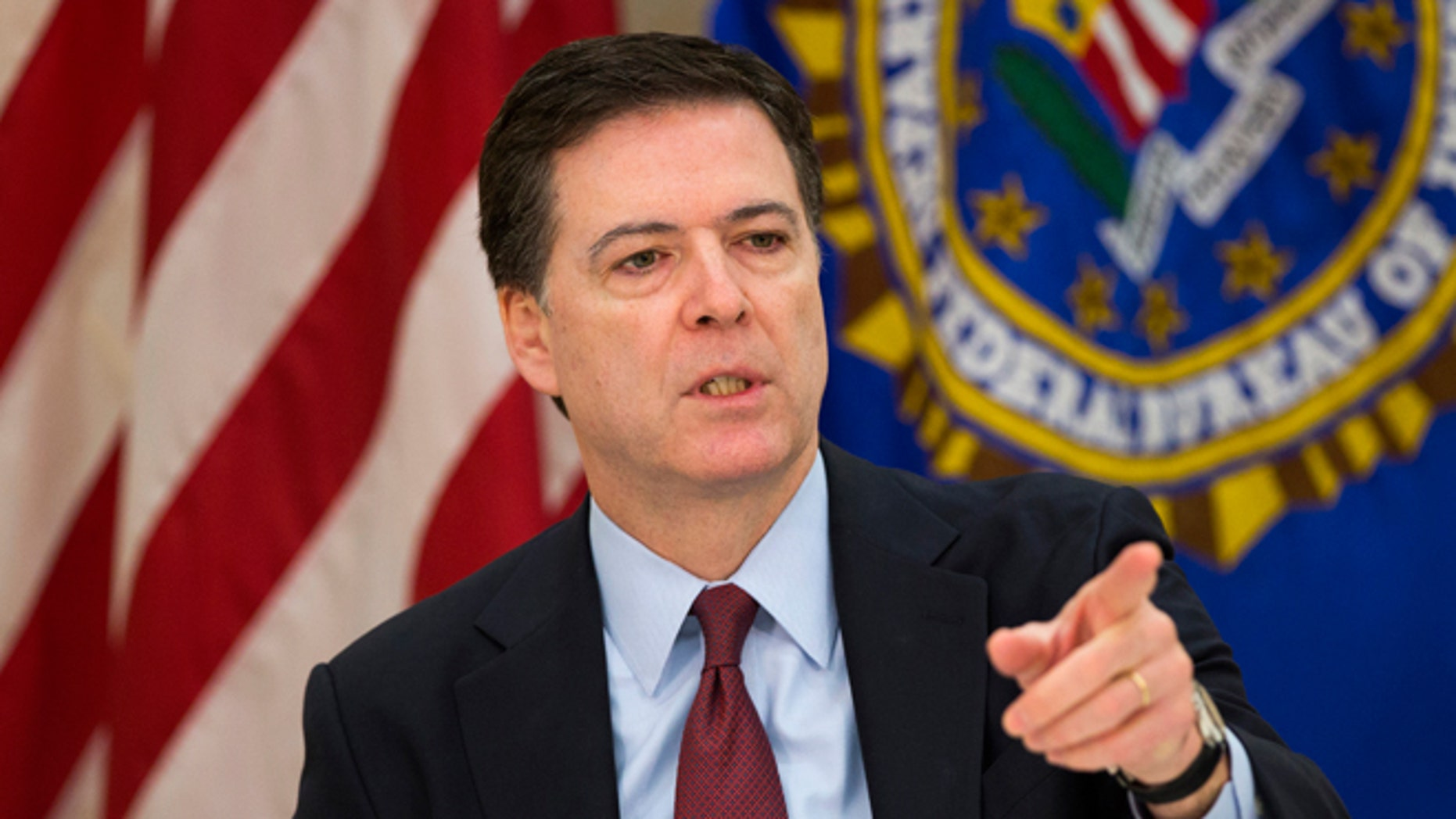 FILE - March 25, 2015: FBI director James Comey as he gestures during a news conference at FBI headquarters in Washington.