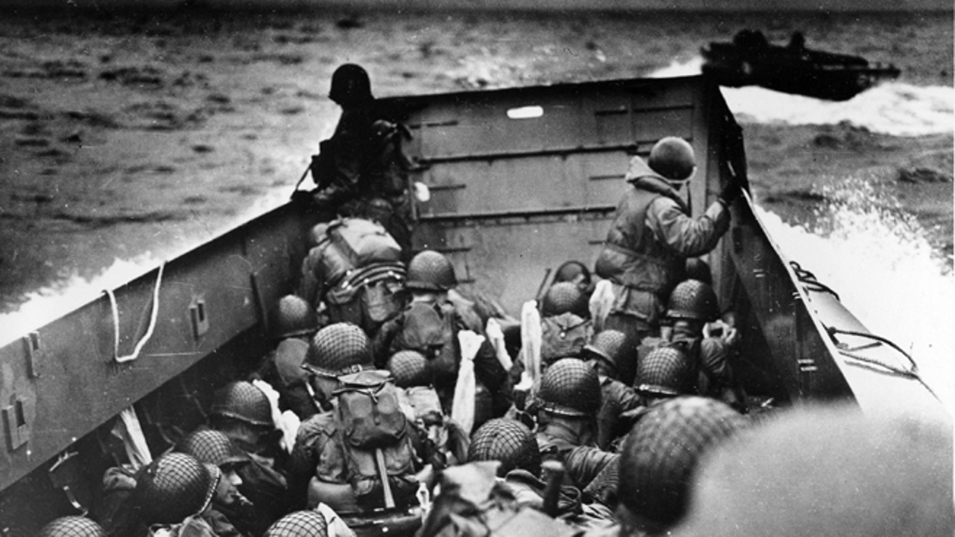 FILE - In this June 6, 2014 file photo, allied troops crouch behind the bulwarks of a landing craft as it nears Omaha Beach during a landing in Normandy, France.