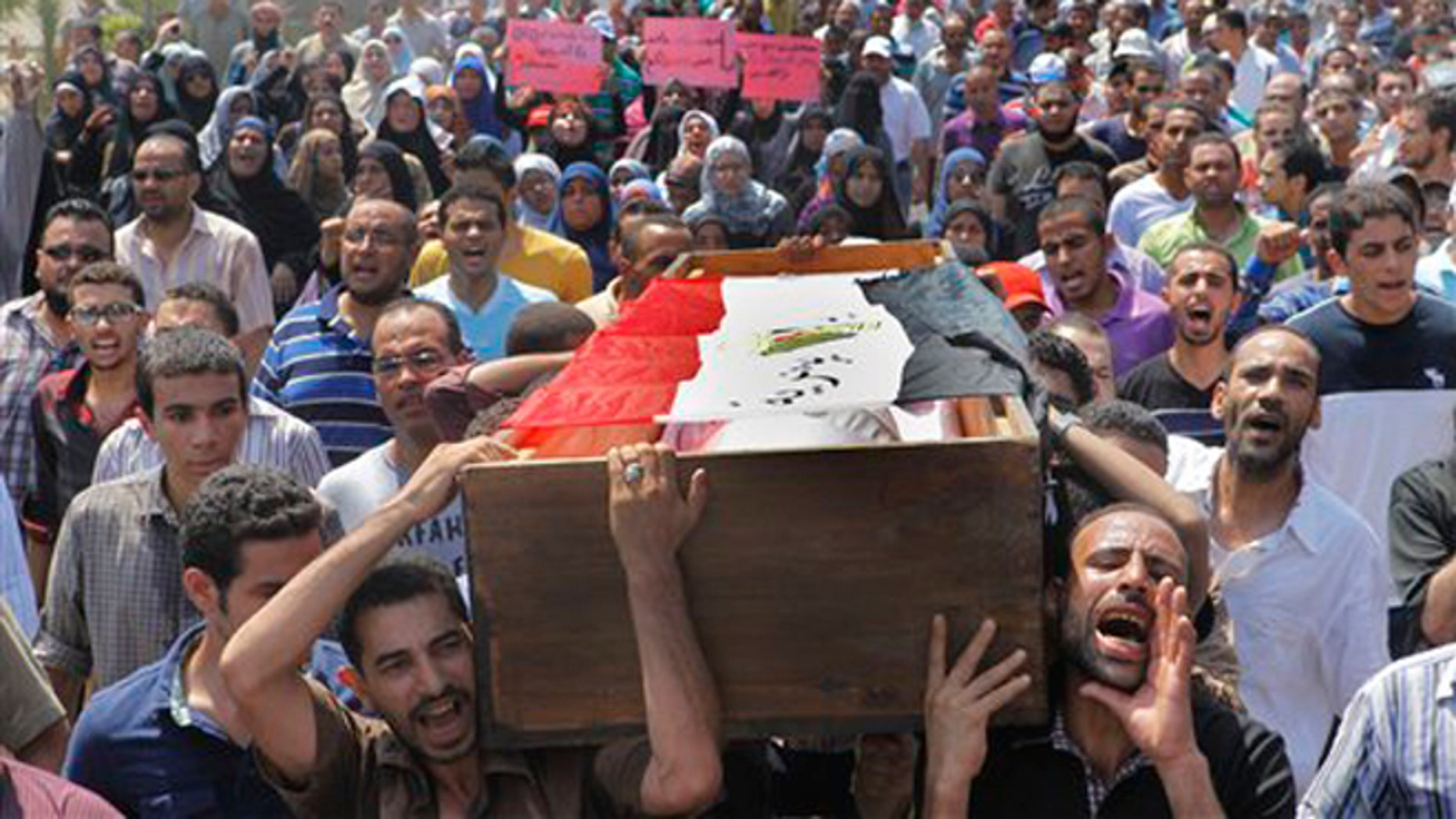 Aug. 16, 2013: Supporters of Egypt's ousted President Mohammed Morsi march towards Old Cairo as they carry the coffin, covered with a national flag, of their colleague who was killed during clashes on August 14 in Cairo, Egypt.