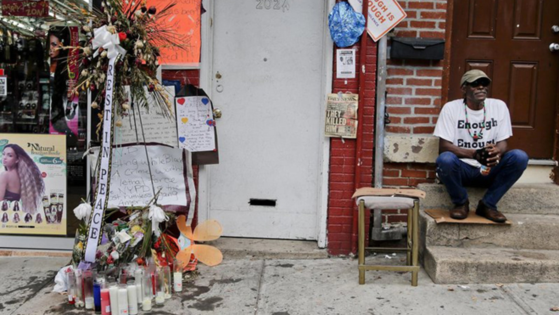 FILE: Doug Brinson sits on a stoop next to a makeshift memorial for Eric Garner in Staten Island, N.Y. Garner died after he was put in a chokehold by police officers while being arrested at the site for selling untaxed loose cigarettes. His death has been ruled a homicide.