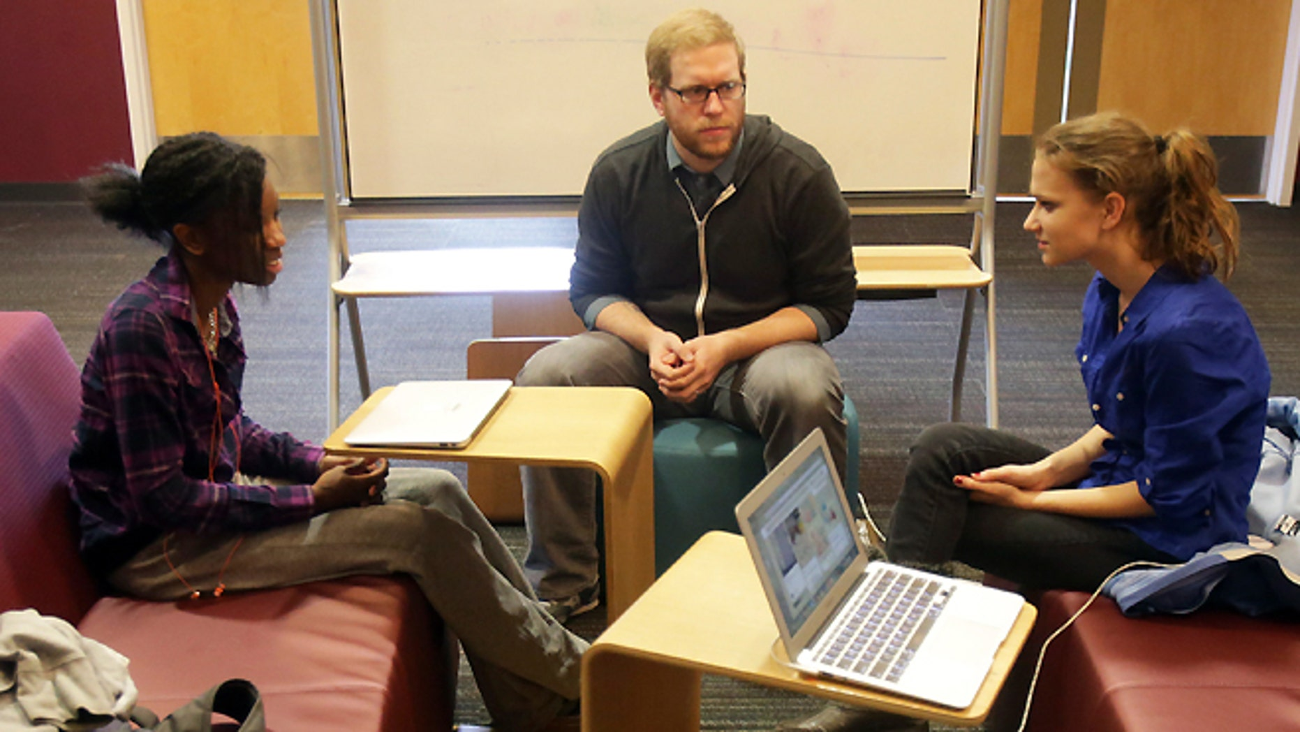 FILE -- English teacher Tom Rademacher talks with his high school juniors Kierra Murray, left, and Ana Silverman, right, at Fair School in Minneapolis.