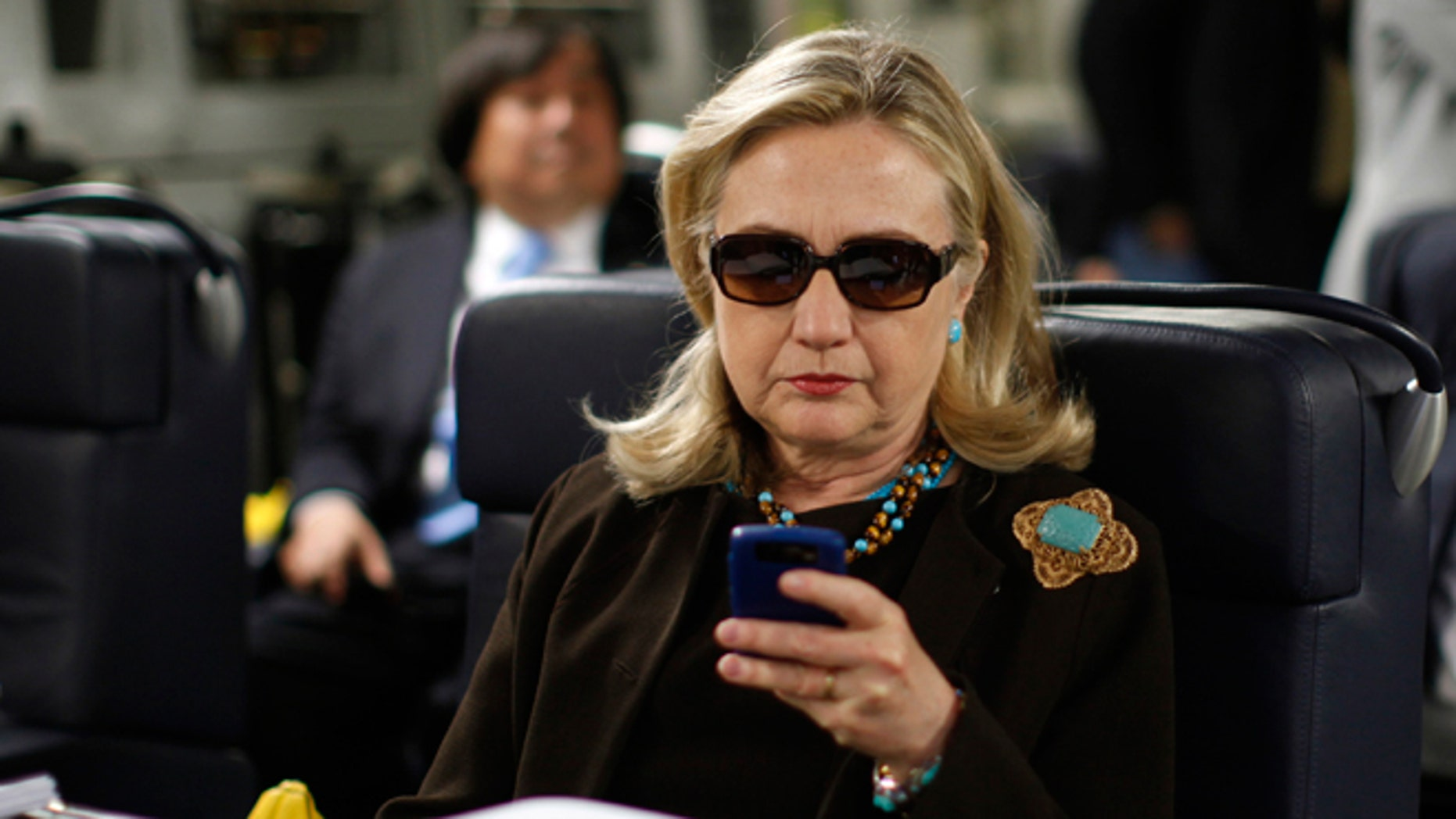 FILE - Oct. 18, 2011: Then-Secretary of State Hillary Rodham Clinton checks her Blackberry from a desk inside a C-17 military plane upon her departure from Malta, in the Mediterranean Sea, bound for Tripoli, Libya.