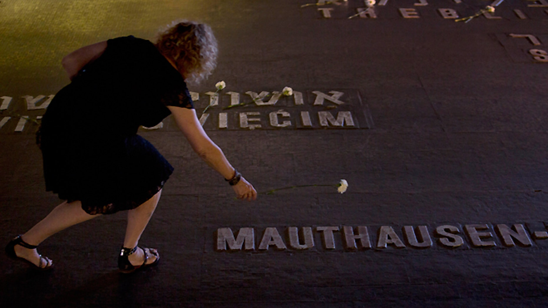 FILE -- April 28, 2014: Relatives of Holocaust victims lay flowers next to the names of concentration camps during a ceremony marking the annual Holocaust Remembrance Day at the Yad Vashem Holocaust Memorial in Jerusalem.