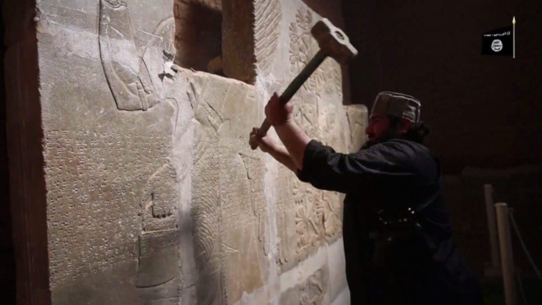 """April 11, 2015: In this image made from video posted on a militant social media account affiliated with the Islamic State group purports to show a militant taking a sledgehammer to an Assyrian relief at the site of the ancient Assyrian city of Nimrud, which dates back to the 13th century B.C., near the militant-held city of Mosul, Iraq. The destruction at Nimrud, follows other attacks on antiquity carried out by the group now holding a third of Iraq and neighboring Syria in its self-declared caliphate. The attacks have horrified archaeologists and U.N. Secretary-General Ban Ki-moon, who last month called the destruction at Nimrud """"a war crime."""""""