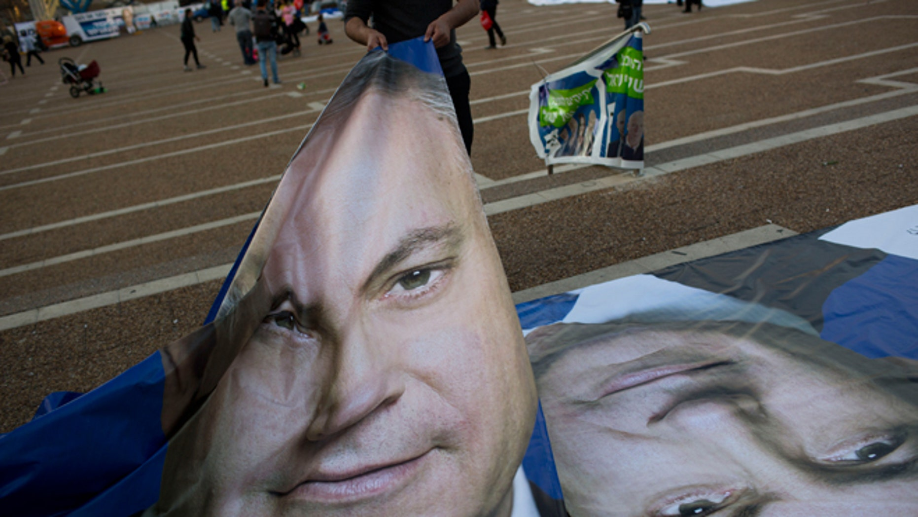 March 15, 2015: People bring posters of Israeli Prime Minister Benjamin Netanyahu prior to his election rally in Tel Aviv, Israel two days ahead of parliament elections. Netanyahu seeks his fourth term as prime minister.