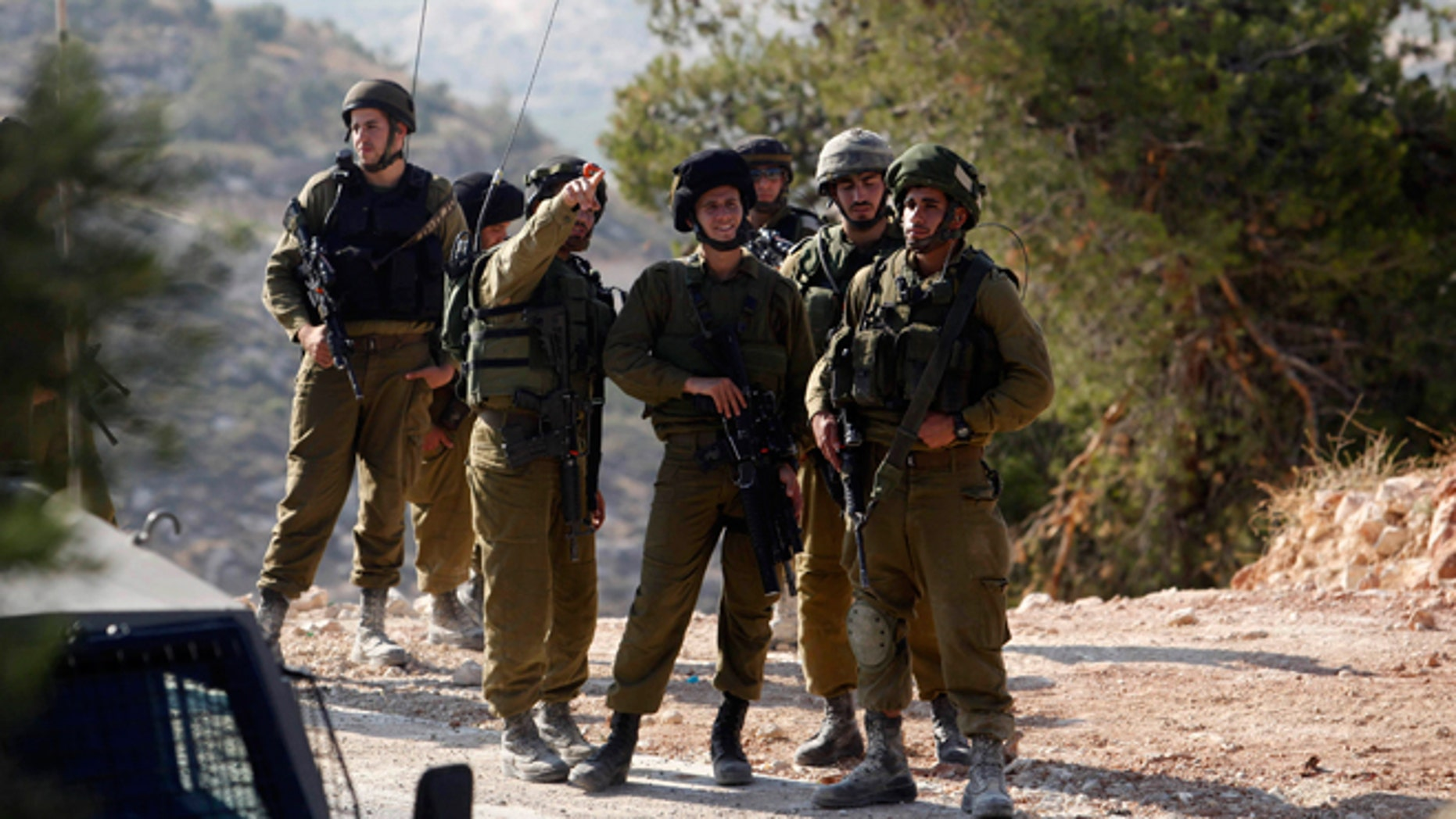 Israeli soldiers deploy near the West Bank city of Hebron, Friday, June 13, 2014. Israeli soldiers searched the West Bank on Friday for three missing teenagers from nearby settlements, one of them a U.S. citizen, amid fears Palestinian militants abducted them, authorities said.