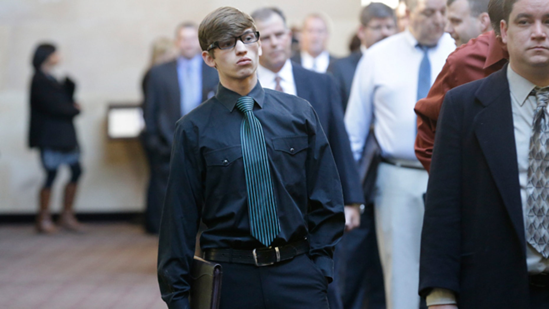 FILE -- Jan. 22, 2014: Austin Moore, 18, lines up with other job seekers during a career fair at a hotel in Dallas.