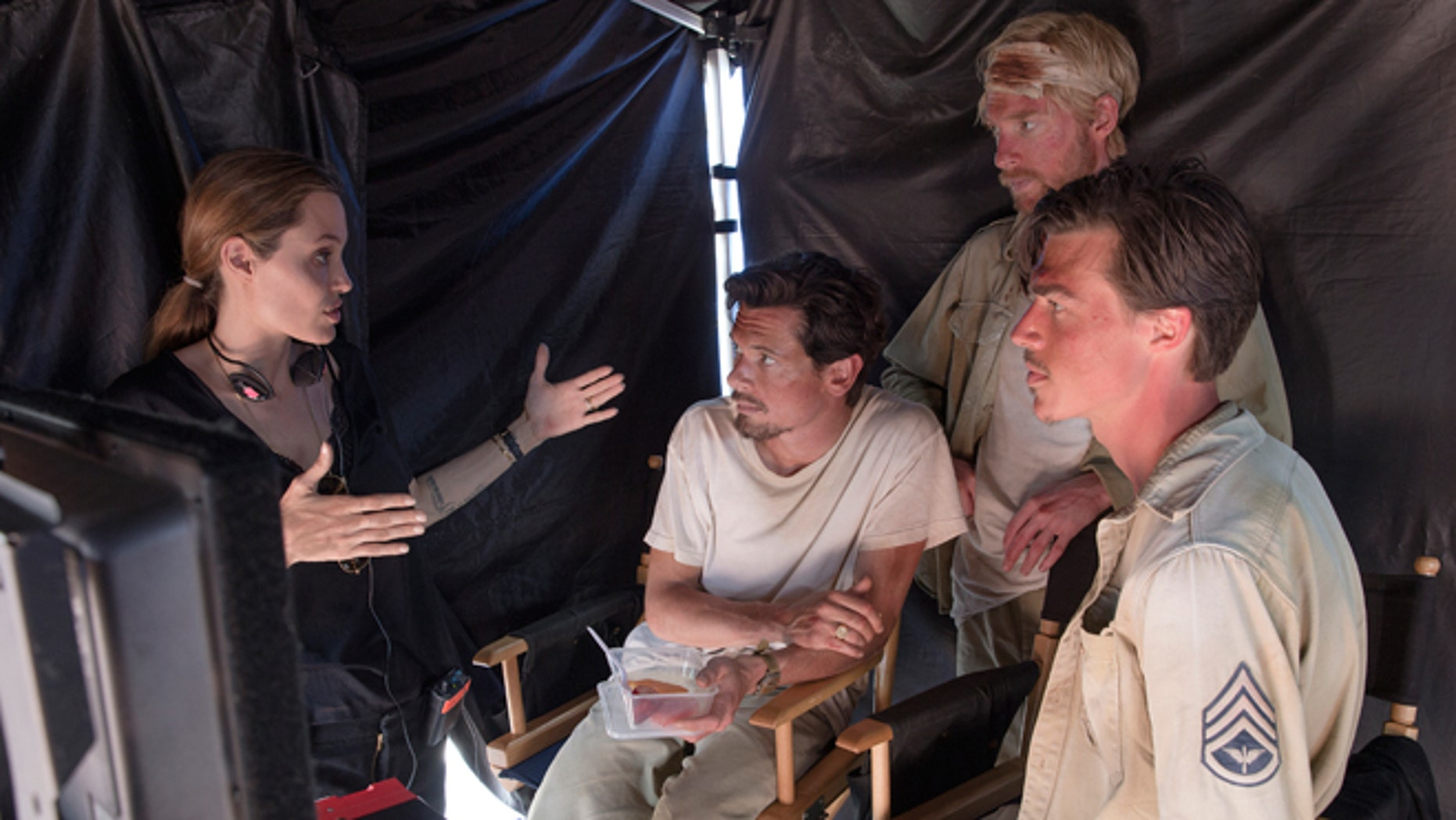 "In this image released by Universal Pictures, director Angelina Jolie, from left, speaks with actors Jack O'Connell, Domhnall Gleeson and Finn Witrock on the set of ""Unbroken."""