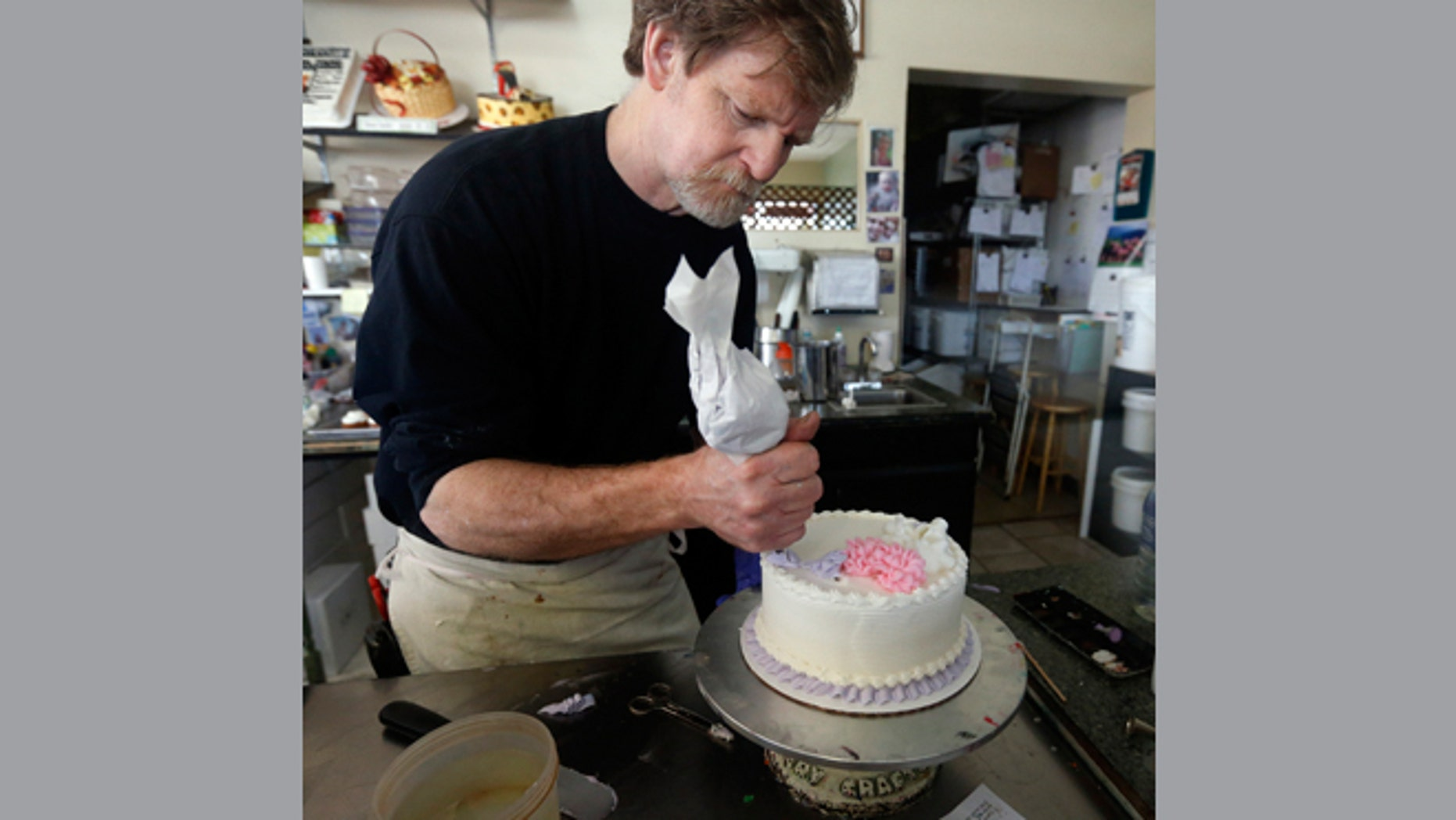 File: March 10, 2014: Masterpiece Cakeshop owner Jack Phillips decorates a cake inside his store, in Lakewood, Colo.