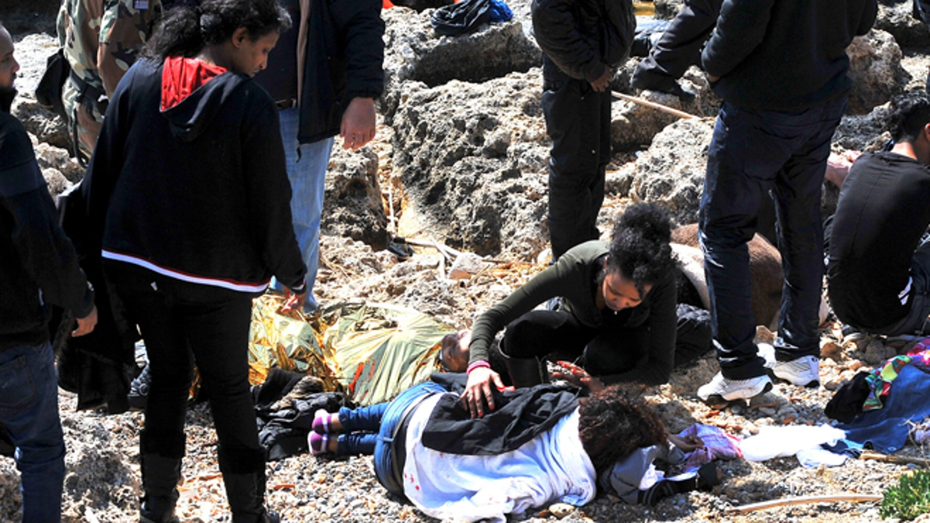 April 20, 2015 : An immigrant treats a co-traveler lying on a coast in the eastern Aegean island of Rhodes, Greece. Greek authorities said that at least three people have died, including a child, after a wooden boat carrying at least 83 migrants from the Turkish shore ran around off the island of Rhodes.