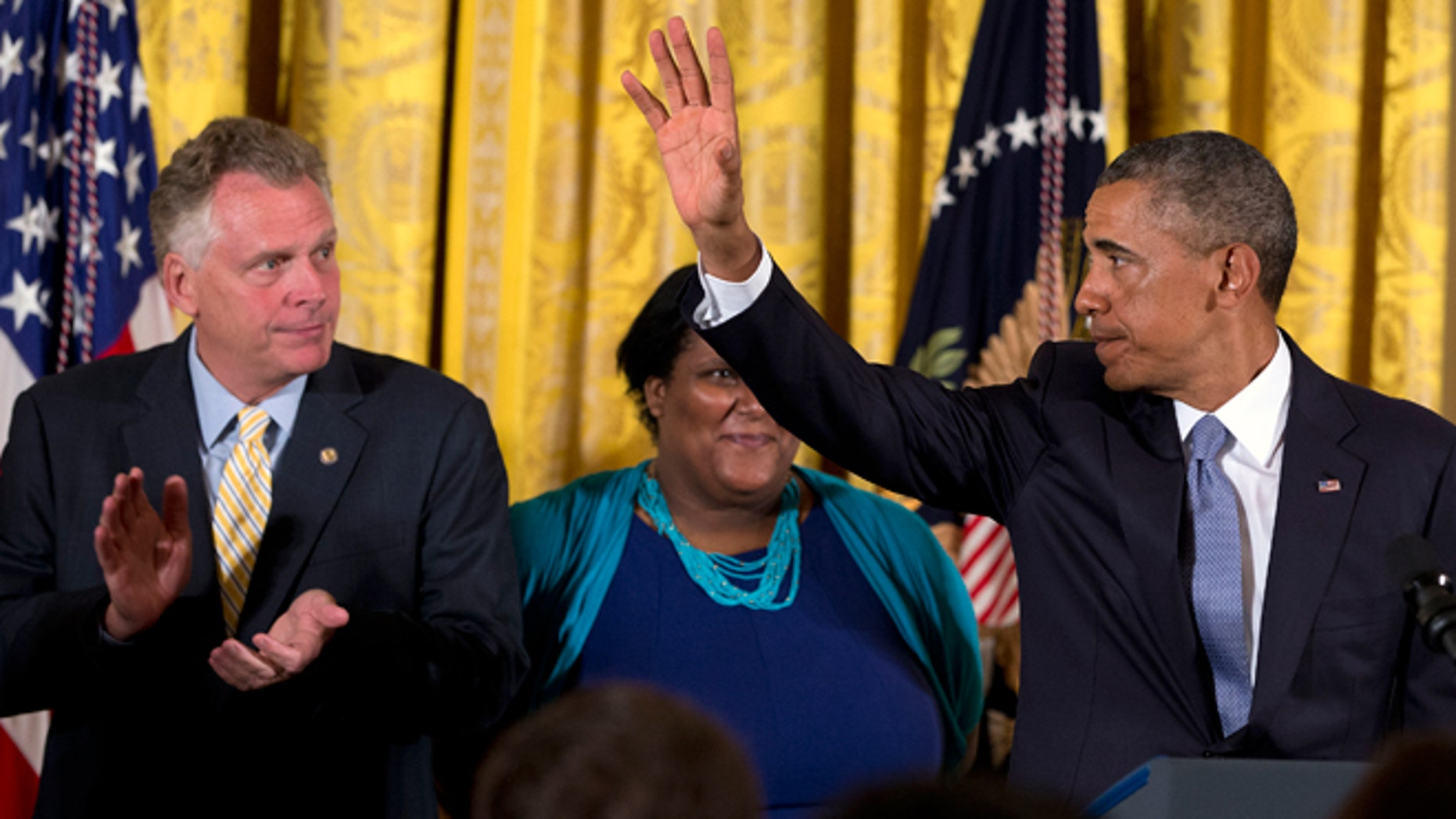 July 21, 2014:  Virginia Governor Terry McAuliffe, left, applauds as President Obama waves after signing an executive order to protect LGBT employees from federal workplace discrimination in the East Room of the White House in Washington. Obama's executive order prohibits discrimination against gay and transgender workers in the federal government and its contracting agencies, without a new exemption that was requested by some religious organizations.