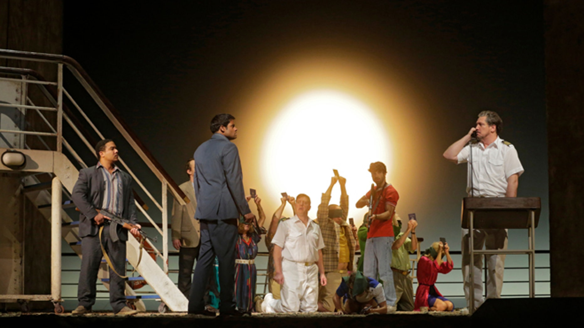 """In this image released by the Metropolitan Opera, Aubrey Allicock as Mamoud, foreground from left, Sean Pannikar as Molqui, and Paulo Szot as the Captain, perform with the cast in """"The Death of Klinghoffer,"""" at the Metropolitan Opera in New York."""