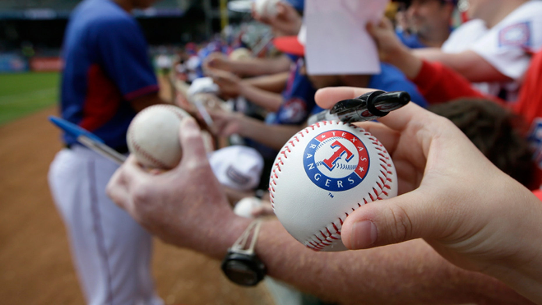 FILE --  March 31, 2014:  A fan holds a Texas Rangers stamped baseball waiting for a autograph from Yu Darvish of Japan before a baseball game against the Philadelphia Phillies in Arlington, Texas.