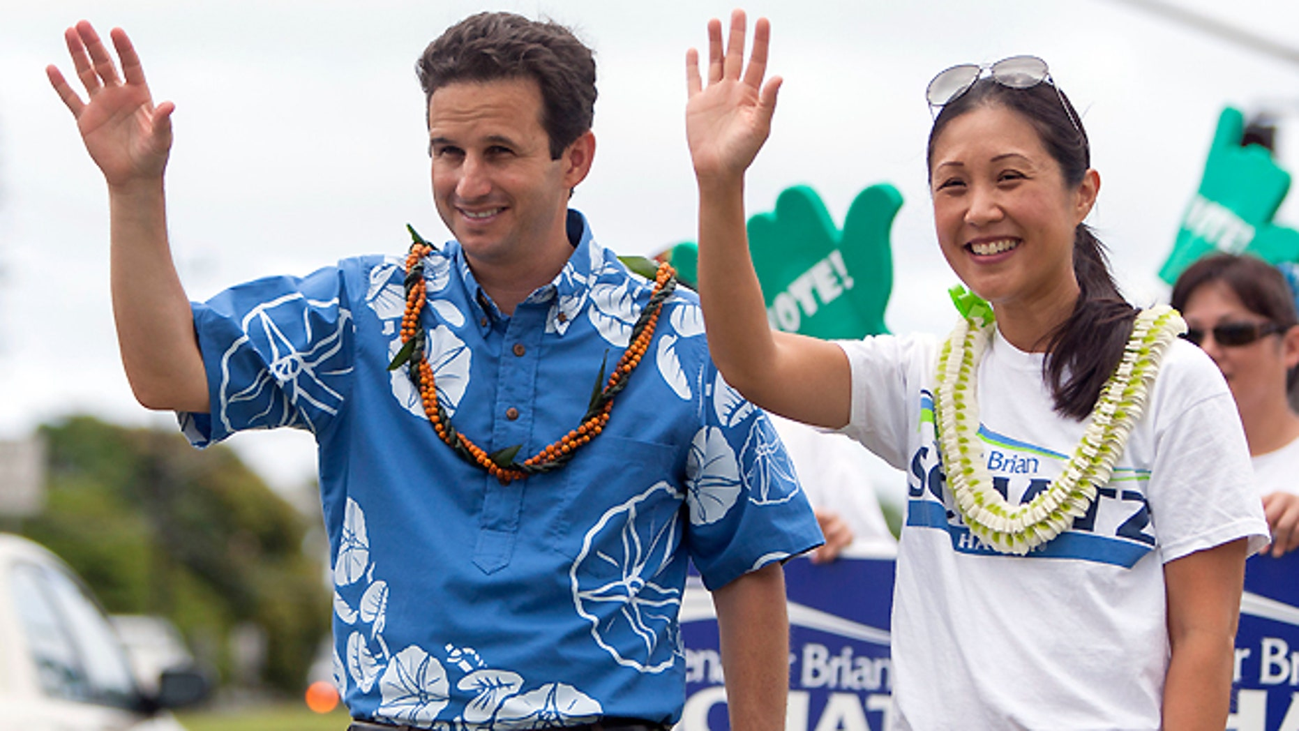 Aug. 9, 2014: U.S. Sen. Brian Schatz, left, and his wife Linda Kwok Schatz gesture to passing cars as he does some last minute campaigning before the primary, Saturday, in Honolulu. Rep. Colleen Hanabusa is challenging incumbent Schatz to determine who will fill the rest of the late Sen. Daniel Inouye's term.
