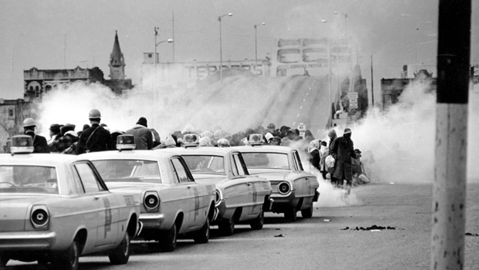 """FILE - March 7, 1965: Clouds of tear gas fill the air as state troopers, ordered by Gov. George Wallace, break up a demonstration march in Selma, Ala., on what became known as """"Bloody Sunday."""" The incident is widely credited for galvanizing the nation's leaders and ultimately yielded passage of the Voting Rights Act of 1965."""