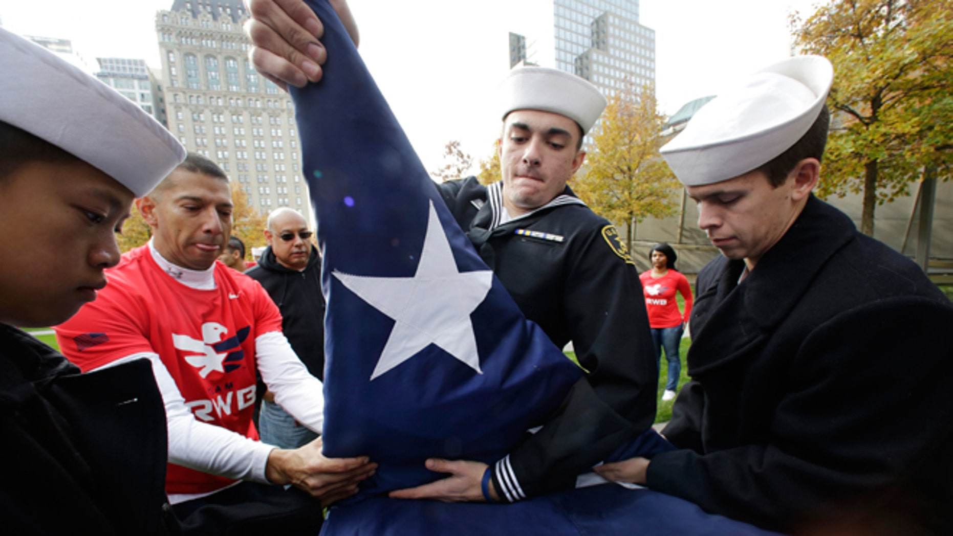 Nov. 9, 2014: Sea Cadets Daniel Cheng, left, Thomas Kessler, center, and Jack Toll help veterans advocacy group Team Red White and Blue furl a large American flag at the National September 11 Memorial in New York. The cadets are members of the John T. Dempster, Jr. Division in Trenton, N.J.