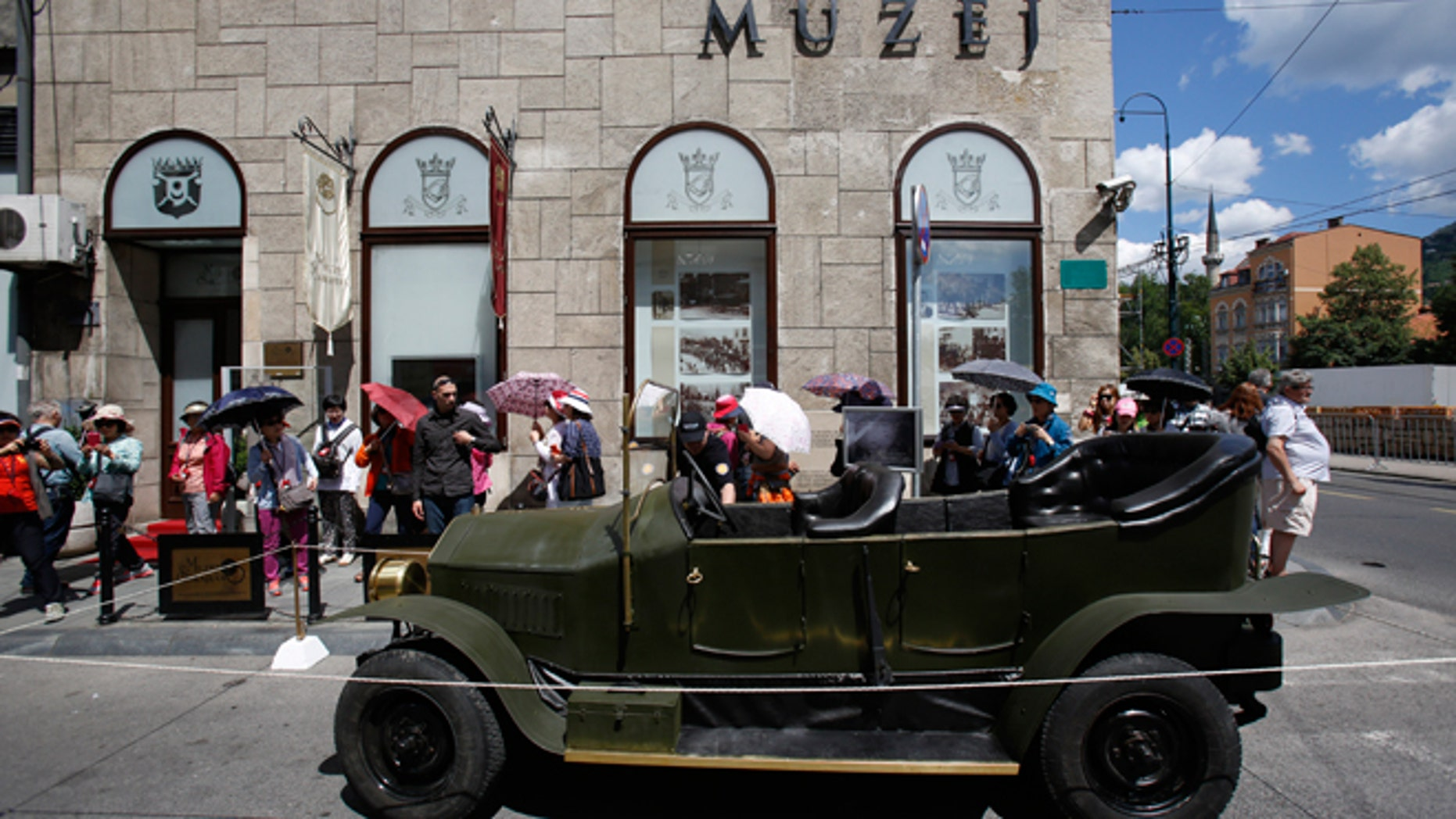 """Tourists gather on Friday, June 27, 2014, around replica of the """"Graf & Stift"""" car that Archduke Franz Ferdinand and his wife Sofia rode in as it is parked in front of museum at the historical street corner in downtown Sarajevo, where Gavrilo Princip, assassinated Austro-Hungarian heir to the throne Archduke Franz Ferdinand and his wife Sofia, on June 28, 1914. The assassination was the event that ignited the start of World War One."""