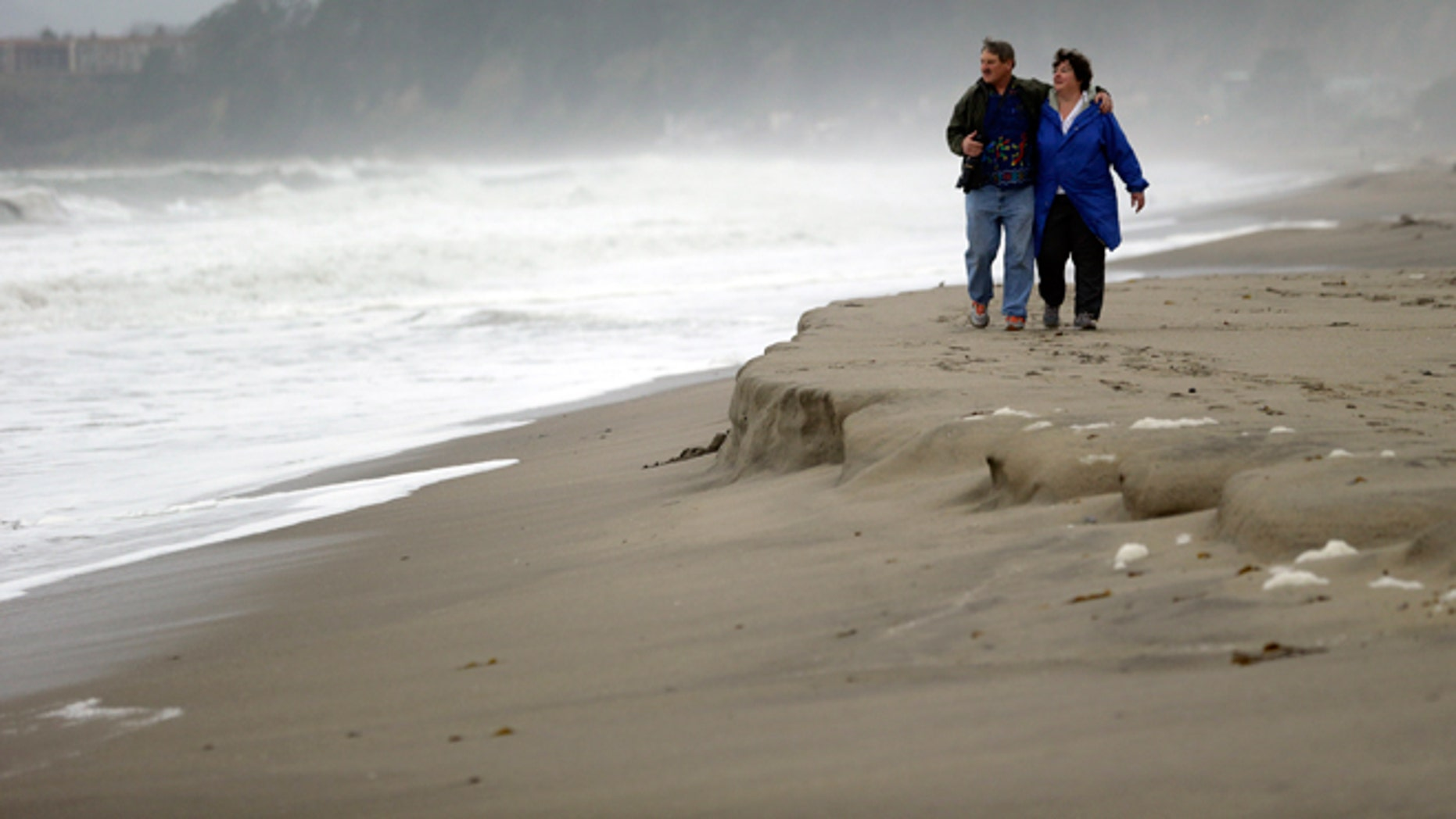 FILE -- Feb. 6, 2015: Ray Matteis, left, and his wife, Penny, walk along the beach at Seacliff State Beach in Aptos, Calif.