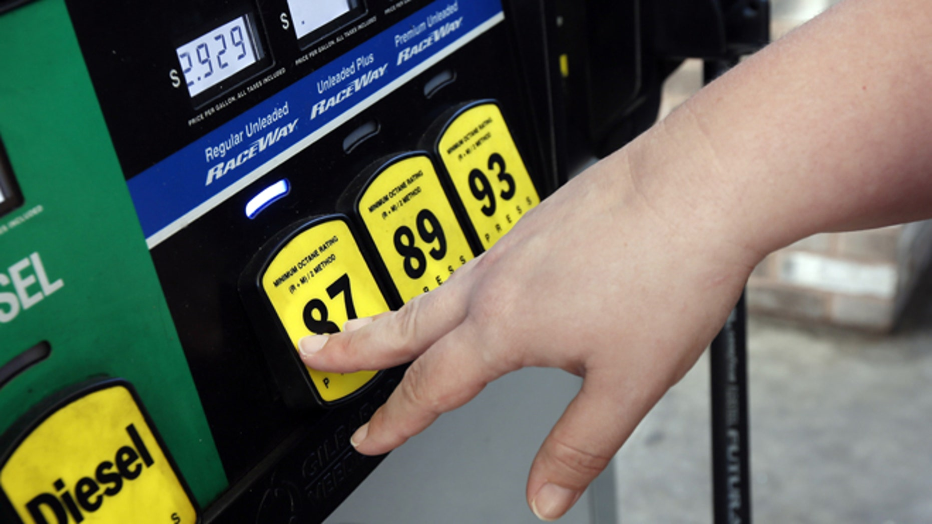FILE -- Sept. 24, 2014: A customer reaches for the regular switch to fill her tank with the $2.92-a-gallon regular gas at a RaceWay gas station in Richland, Miss.