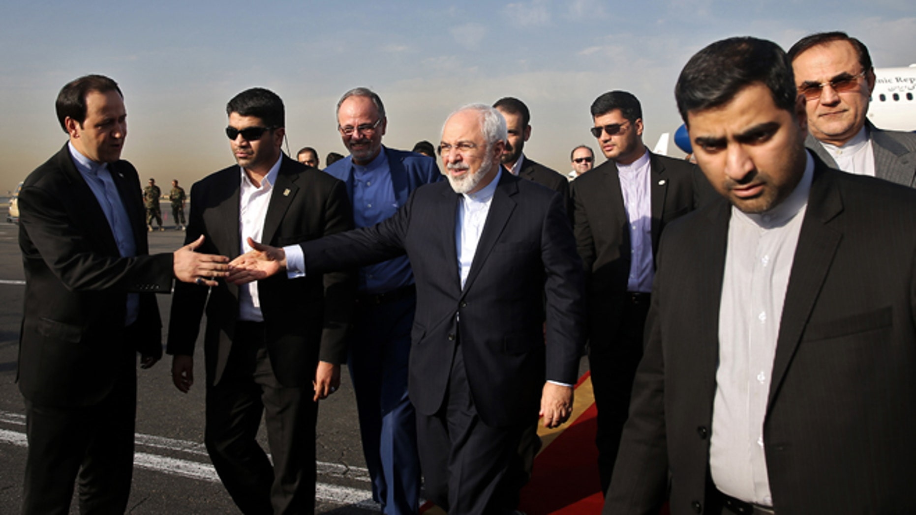 July 15, 2015: Iran's Foreign Minister Mohammad Javad Zarif, who is also Iran's top nuclear negotiator, center, shakes hands with an official upon arrival at the Mehrabad airport in Tehran, Iran. (AP Photo/Ebrahim Noroozi)