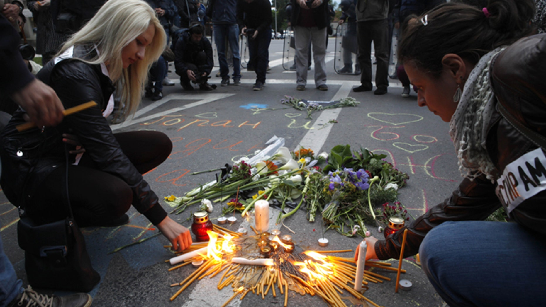 May 11, 2015: People light candles and lay flowers as police officers stand guard in front of the government building in Skopje, Macedonia. A group of people gathered peacefully in Skopje for the eight police officers who were killed and 37 more were wounded in an exchange of fire between special police forces and an armed group that started in Macedonian northern town of Kumanovo on Saturday. Fighting between police forces and members of an armed group in Kumanovo ended Sunday after two days leaving 8 police officers and 14 armed suspected terrorists dead. AP Photo/Boris Grdanoski