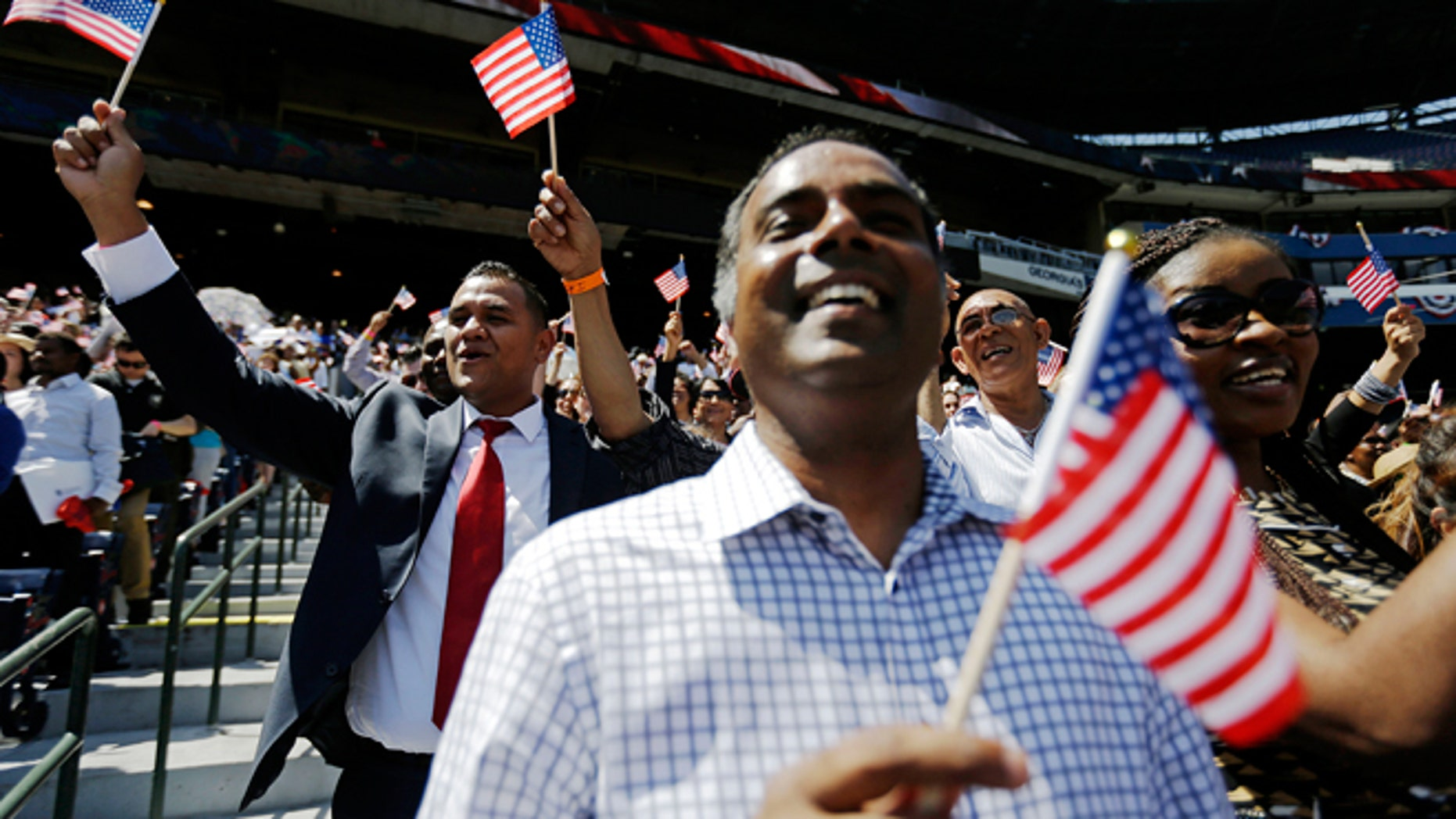 July 2, 2014: Newly-sworn in U.S. citizens cheer during a naturalization ceremony for more than 1,000 citizenship candidates at Turner Field, home of the Atlanta Braves baseball team, in Atlanta. U.S. Citizenship and Immigration Services welcomed 1,094 new citizens from 81 countries as part of their annual Independence Day celebration marking the nation's 238th birthday this year.