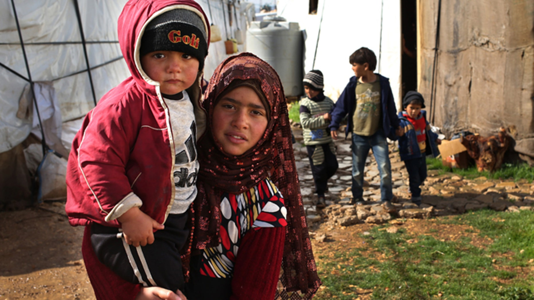 FILE -- March 12, 2014: A Syrian girl, foreground, carries her brother and walks between tents with other children, background, on their way to a makeshift school at their refugee encampment in the Lebanese-Syrian border town of Majdal Anjar, eastern Bekaa valley, Lebanon. More than 2 million of those who should be in school remain in Syria, where classrooms have been bombed, used as shelters or turned into military barracks. Another 300,000 Syrian children don't attend school in Lebanon, along with some 93,000 in Jordan, 78,000 in Turkey, 26,000 in Iraq and 4,000 in Egypt, UNICEF officials in Geneva said. Those numbers likely are higher, as UNICEF can't count the children whose parents didn't register with the United Nations refugee agency.