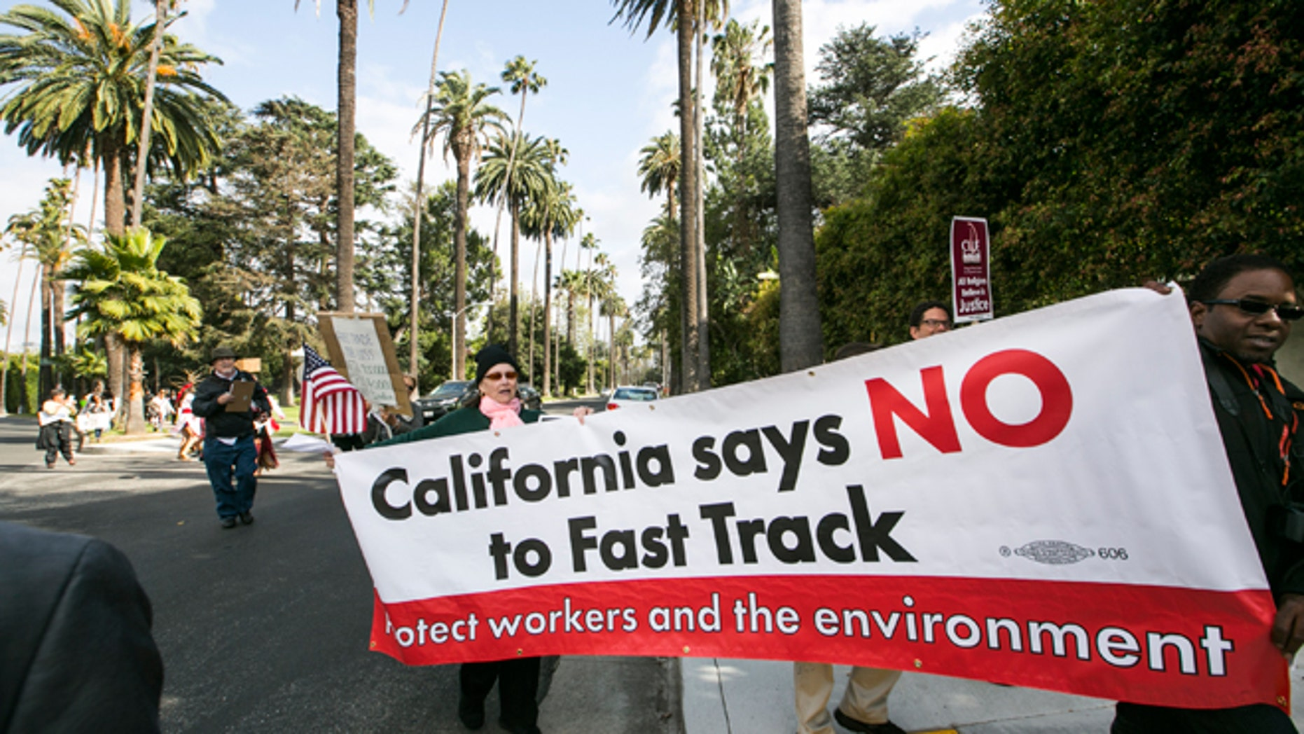 """May 7, 2015: Los Angeles community members take to the streets of Beverly Hills to demand that Hillary Rodham Clinton oppose the Trans-Pacific Partnership (TPP) and Trade Promotion Authority (TPA) known as """"The Fast Track,"""" in Beverly Hills, Calif. AP Photo/Damian Dovarganes"""