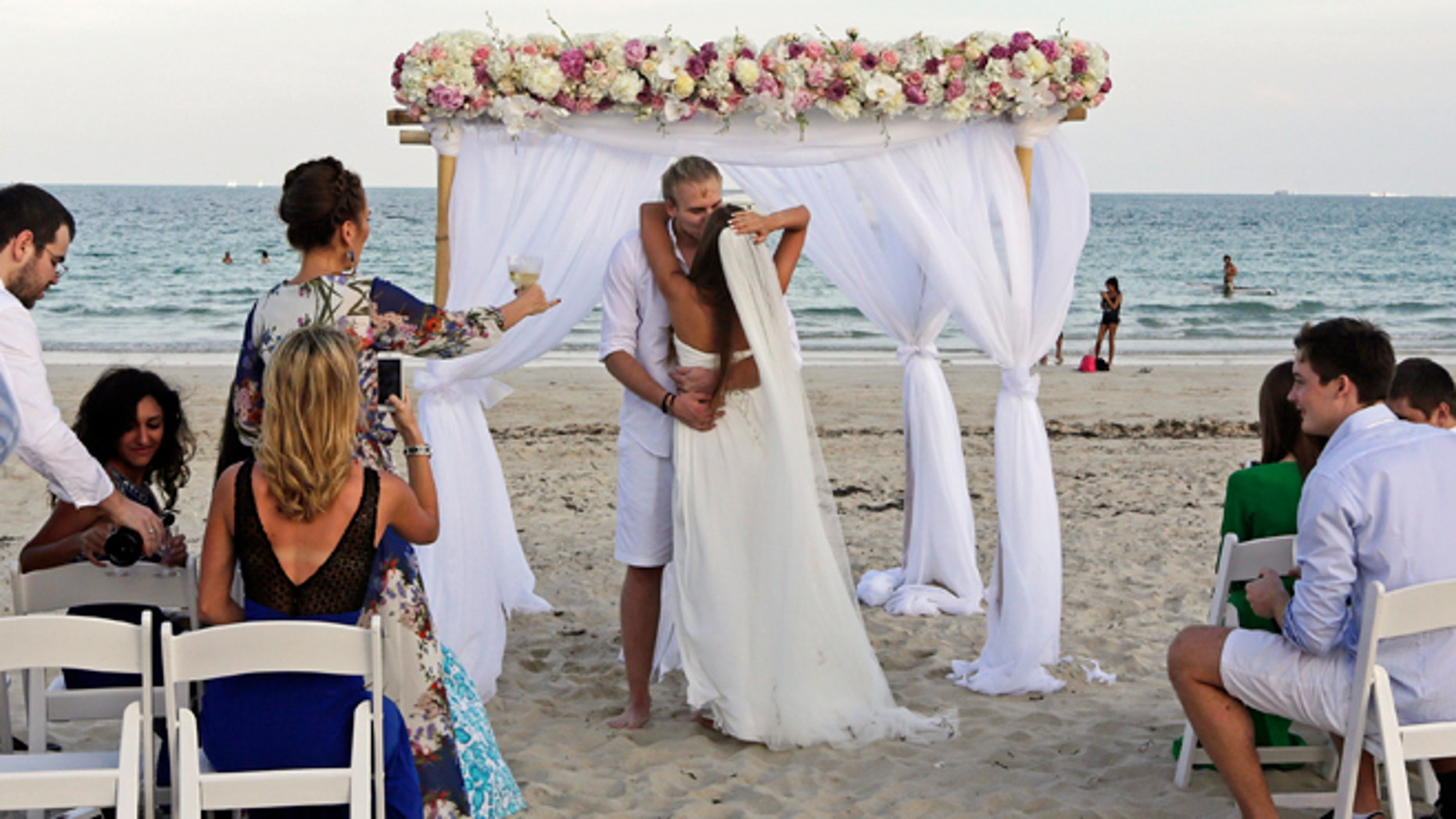 FILE -- Jan. 7, 2015: Tourists Vlad Borankin, the groom, and Daria Borankina, both of Moscow, Russia, kiss during their wedding ceremony at South Pointe area in Miami Beach, Fla.
