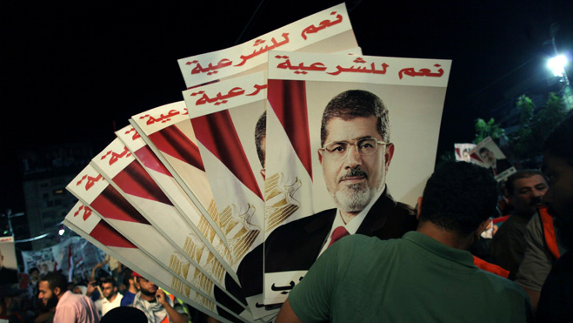 """Aug. 6, 2013: A supporter of Egypt's ousted President Mohammed Morsi holds his posters with Arabic writing which reads """"Yes for legality""""; during a protest outside Rabaah al-Adawiya mosque, where protesters have installed a camp and hold daily rallies at Nasr City in Cairo, Egypt."""