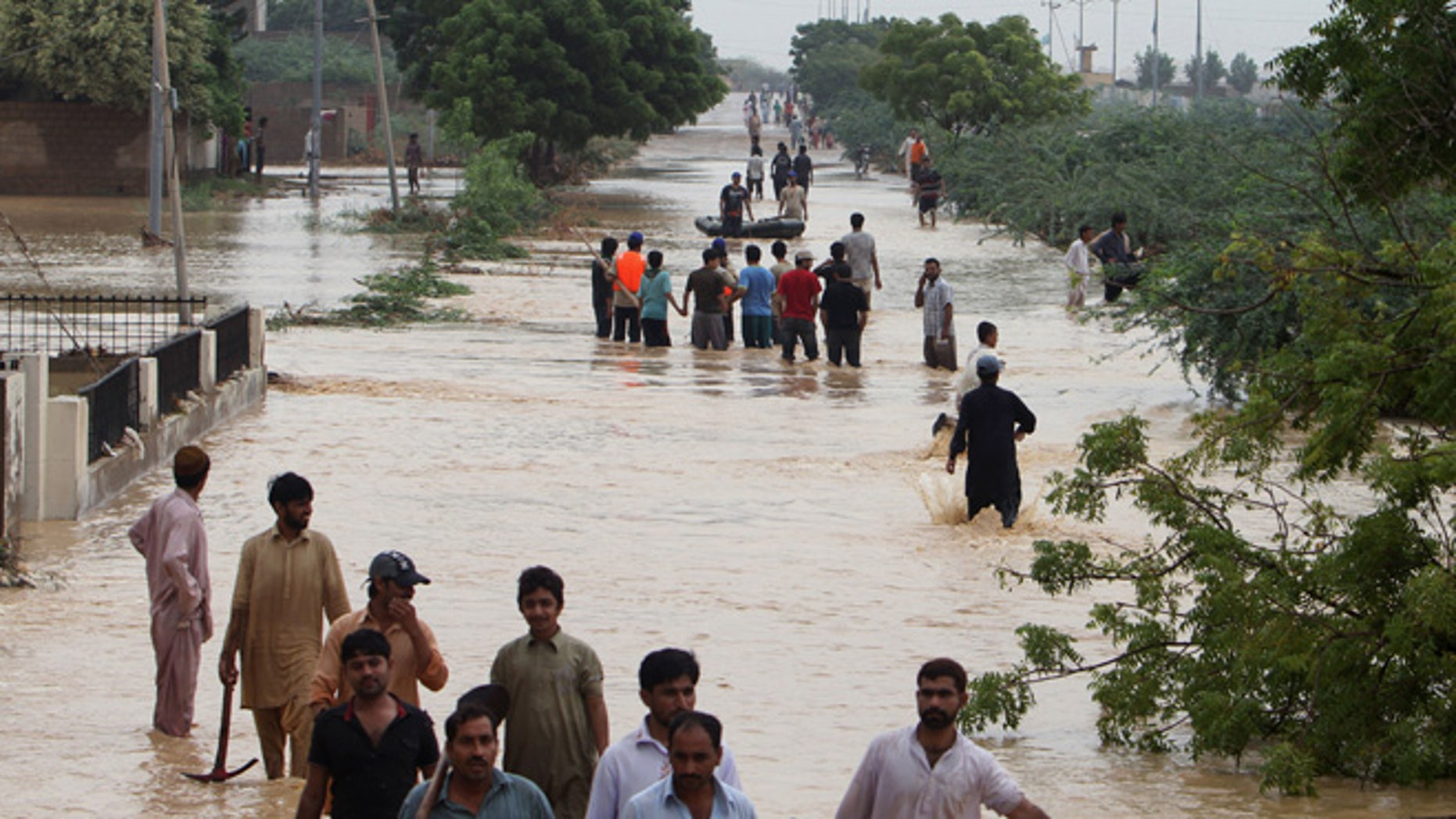 Aug. 4, 2013: People wade through flooded road caused by heavy rains on the outskirts of Karachi, Pakistan.