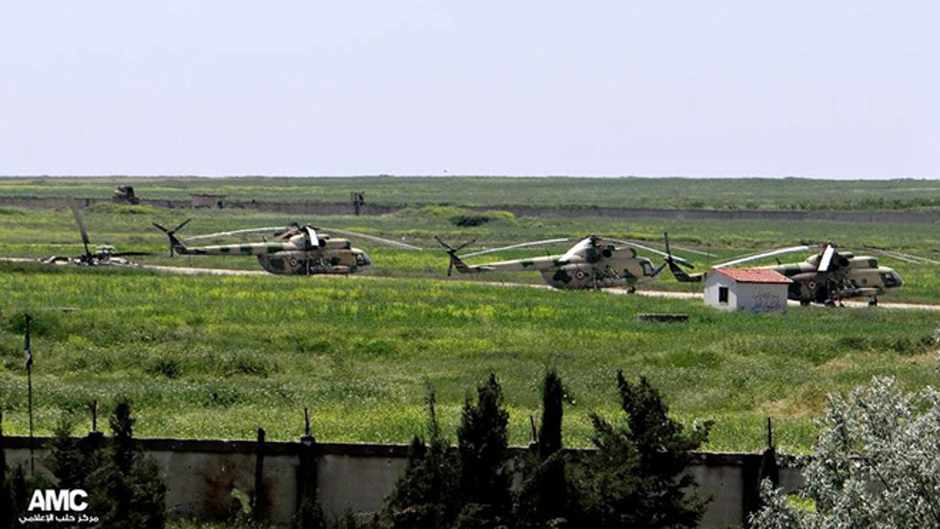 June 18, 2013: This file photo, citizen journalism image provided by Aleppo Media Center AMC which has been authenticated based on its contents and other AP reporting, shows Syrian military helicopters at Mannagh air base in Aleppo province, Syria.