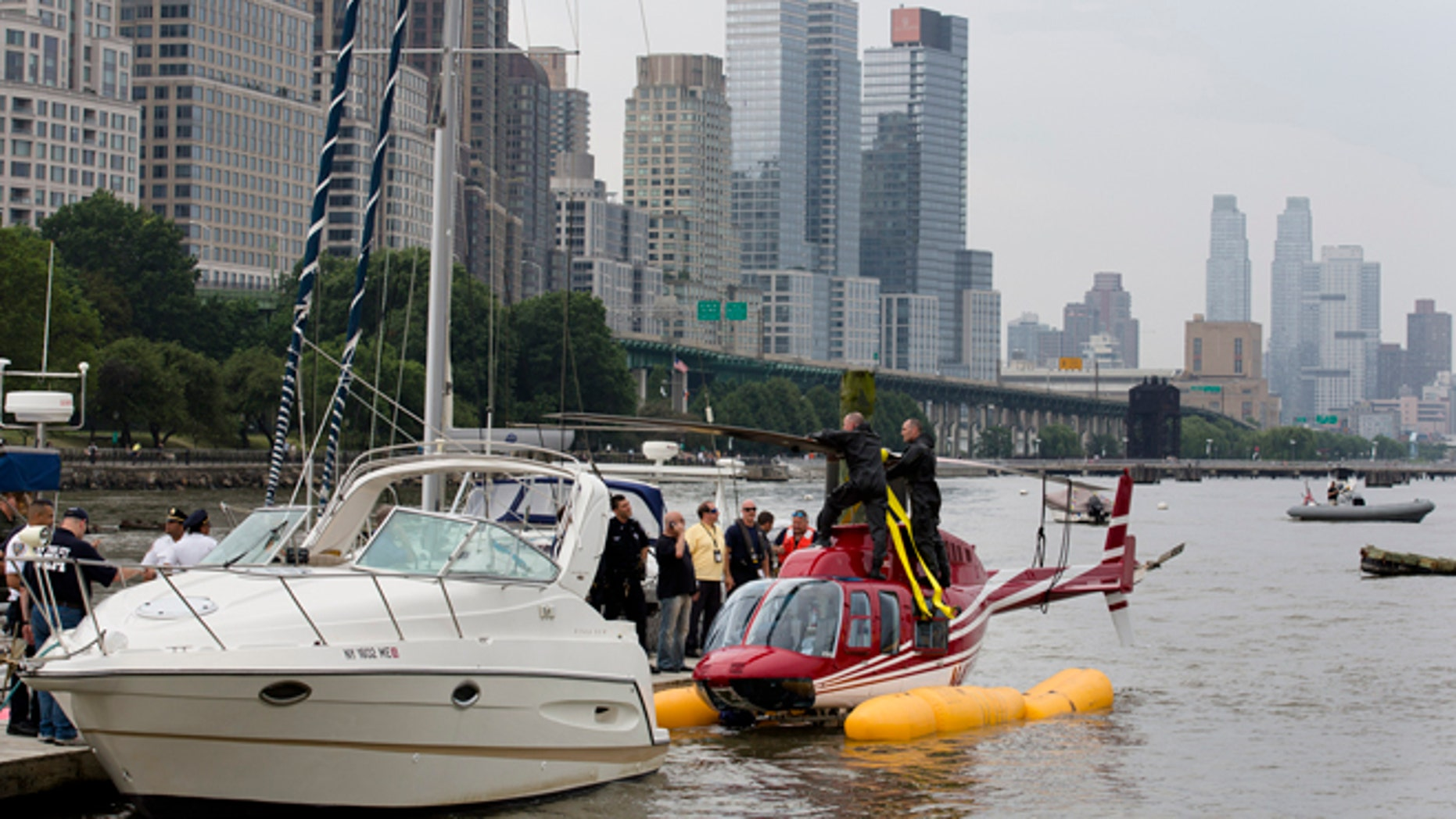 June 30, 2013: A helicopter rests on a pontoon at the 79th Street Boat Basin after emergency landing over the Hudson river in New York.