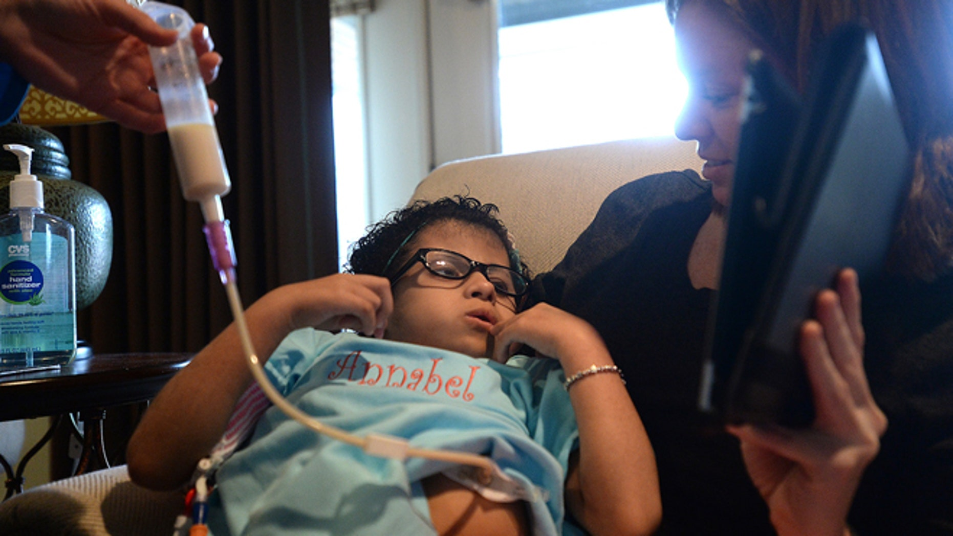 Annabel Shelander watches an episode of Barney with older sister Tara as nurse aide Megan Goats gives her a feeding through her peg tube at the family's home in Beaumont, Texas, on Saturday, Feb. 14, 2015.  Shelander, 9, has a rare condition that keeps her from consuming and digesting food naturally.  (AP Photo/The Beaumont Enterprise, Kim Brent)