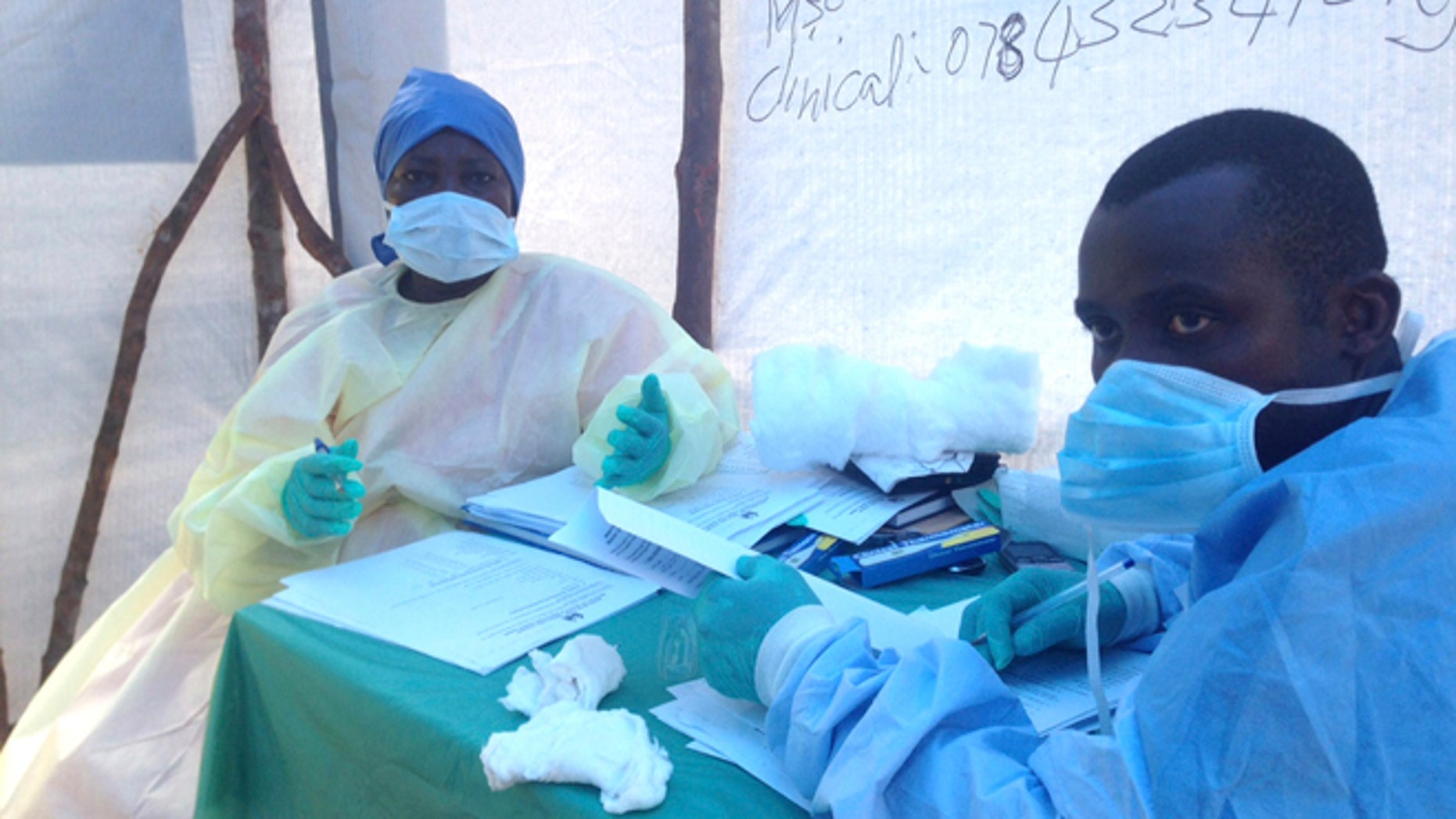 Government health workers are seen during the administration of blood tests for the Ebola virus in Kenema, Sierra Leone, June 25, 2014.