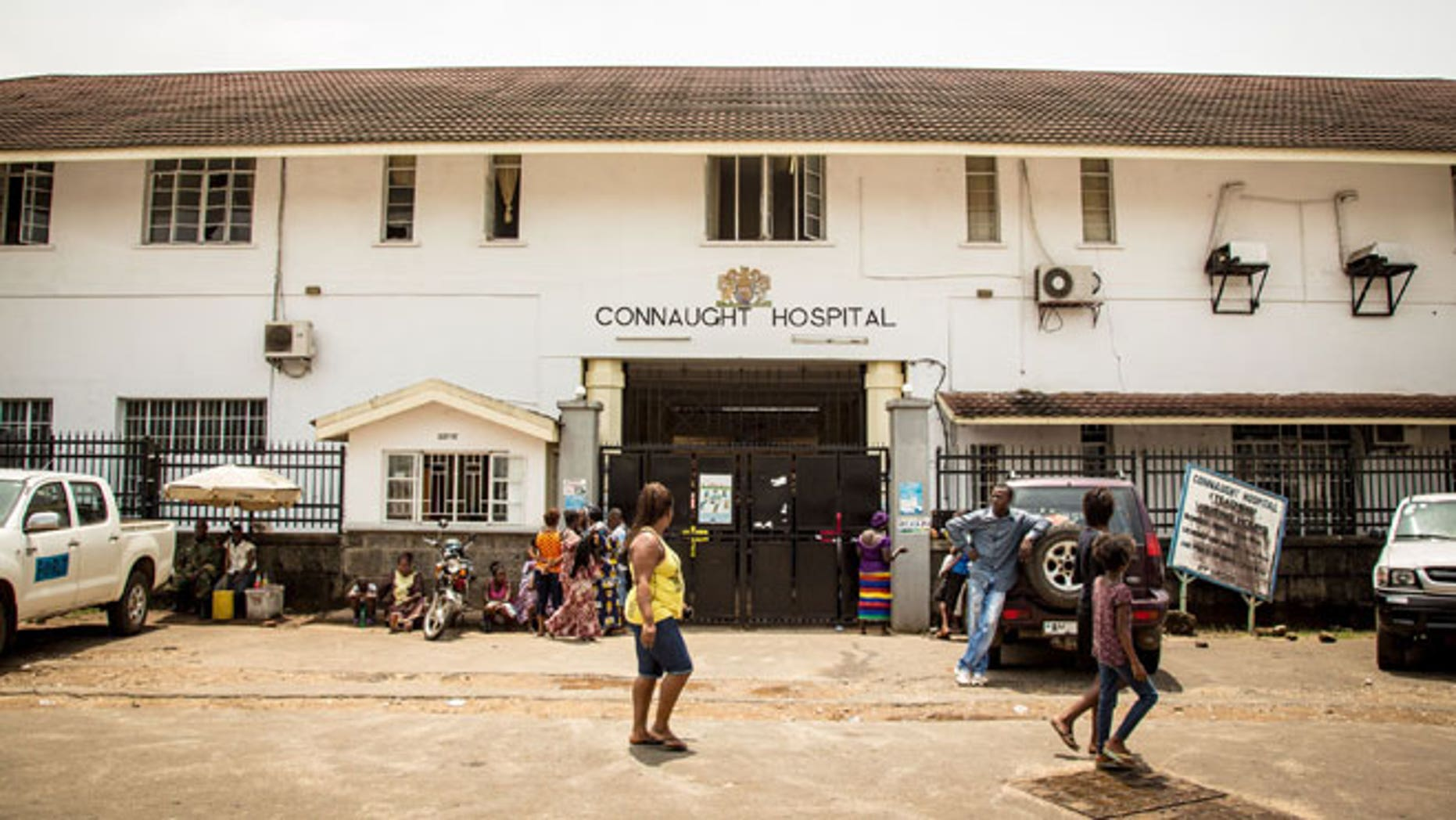 In this photo taken on Sunday, Sept. 14, 2014, people walk past the Connaught Hospital that is used for treating people suffering from the Ebola virus in Freetown, Sierra Leone.
