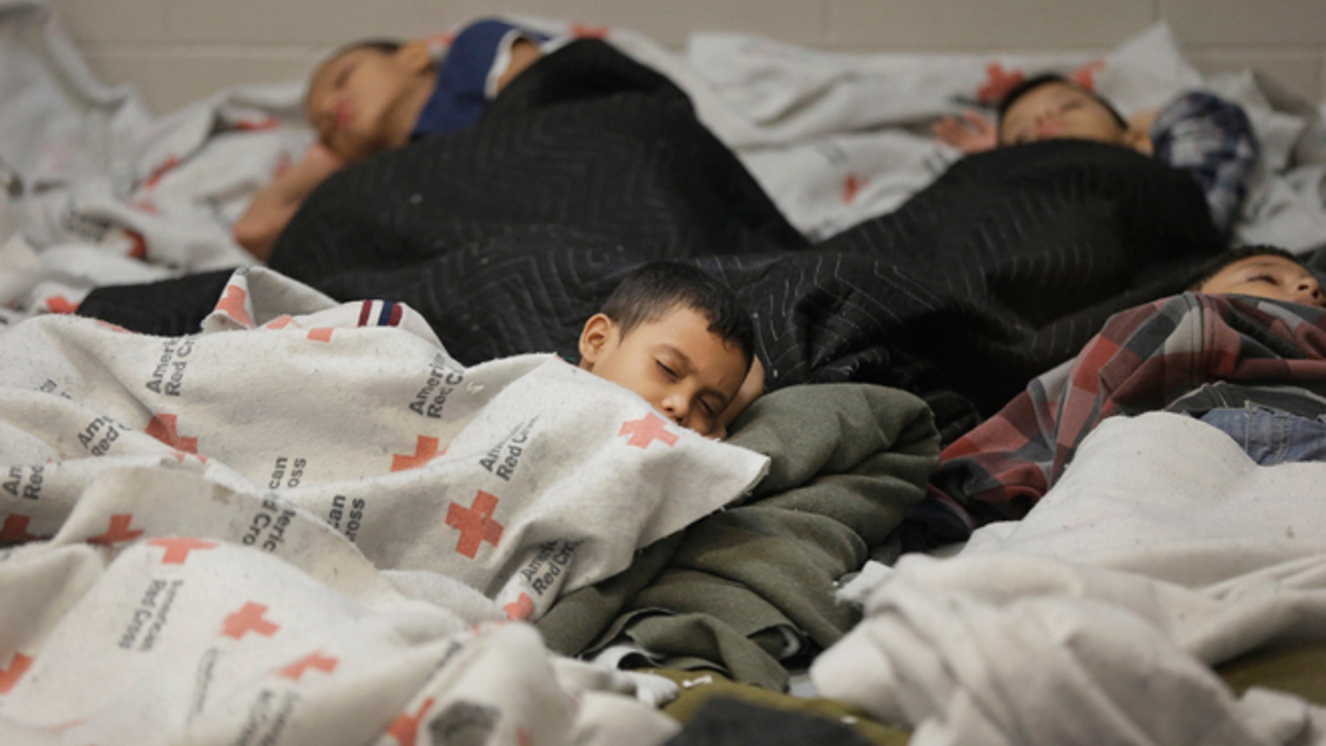 Detainees sleep in a holding cell at a U.S. Customs and Border Protection processing facility, in Brownsville, Texas June 18, 2014. CPB provided media tours June 18 of two locations in Brownsville and Nogales, Arizona that have been central to processing the more than 47,000 unaccompanied children who have entered the country illegally since Oct. 1.  REUTERS/Eric Gay/Pool  (UNITED STATES - Tags: CRIME LAW POLITICS SOCIETY) - RTR3UI3Q