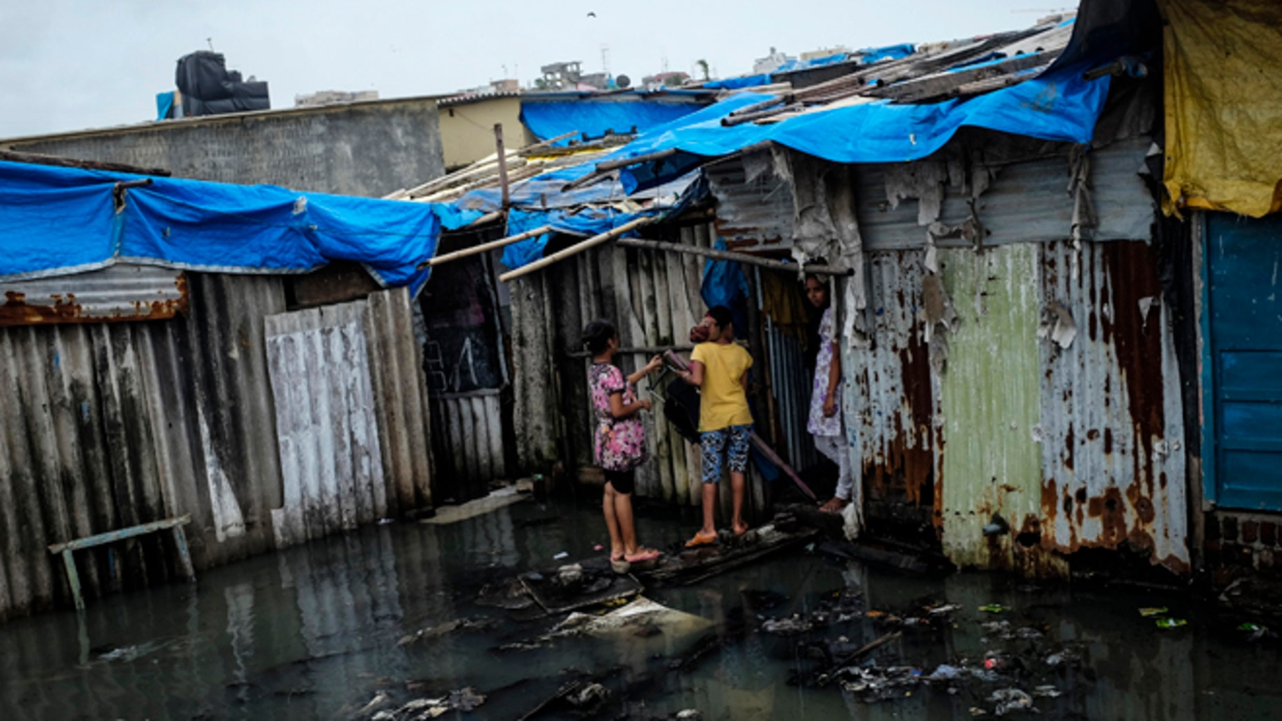 Residents stand in a flooded street outside their house at a slum in Mumbai July 16, 2014. Weak rainfall in India since the start June, when the monsoon season began, has raised concerns of a first drought in five years, although weather experts are hopeful rains will revive in the next week. REUTERS/Danish Siddiqui (INDIA - Tags: SOCIETY ENVIRONMENT POVERTY) - RTR3YWFK