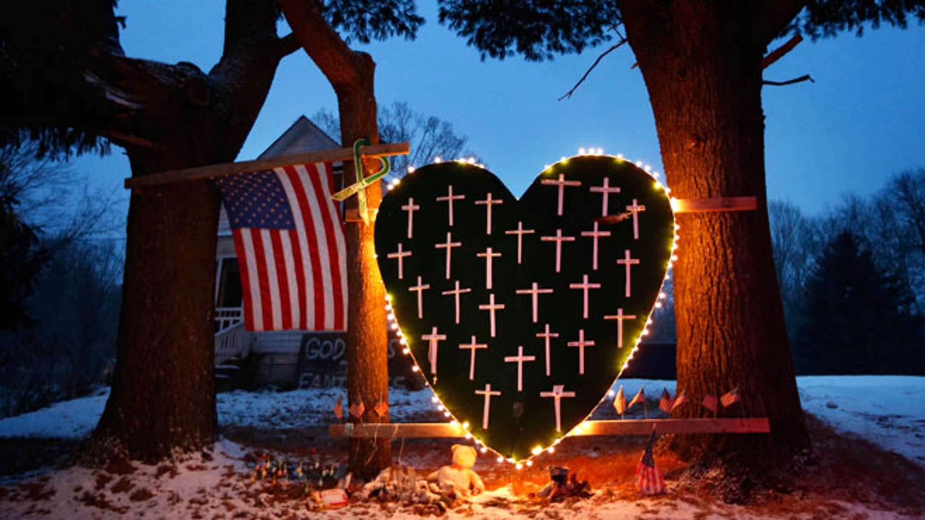 A makeshift memorial with crosses for the victims of the Sandy Hook Elementary School shooting massacre stands outside a home in Newtown, Conn., on the one-year anniversary of the shootings, Dec. 14, 2013.