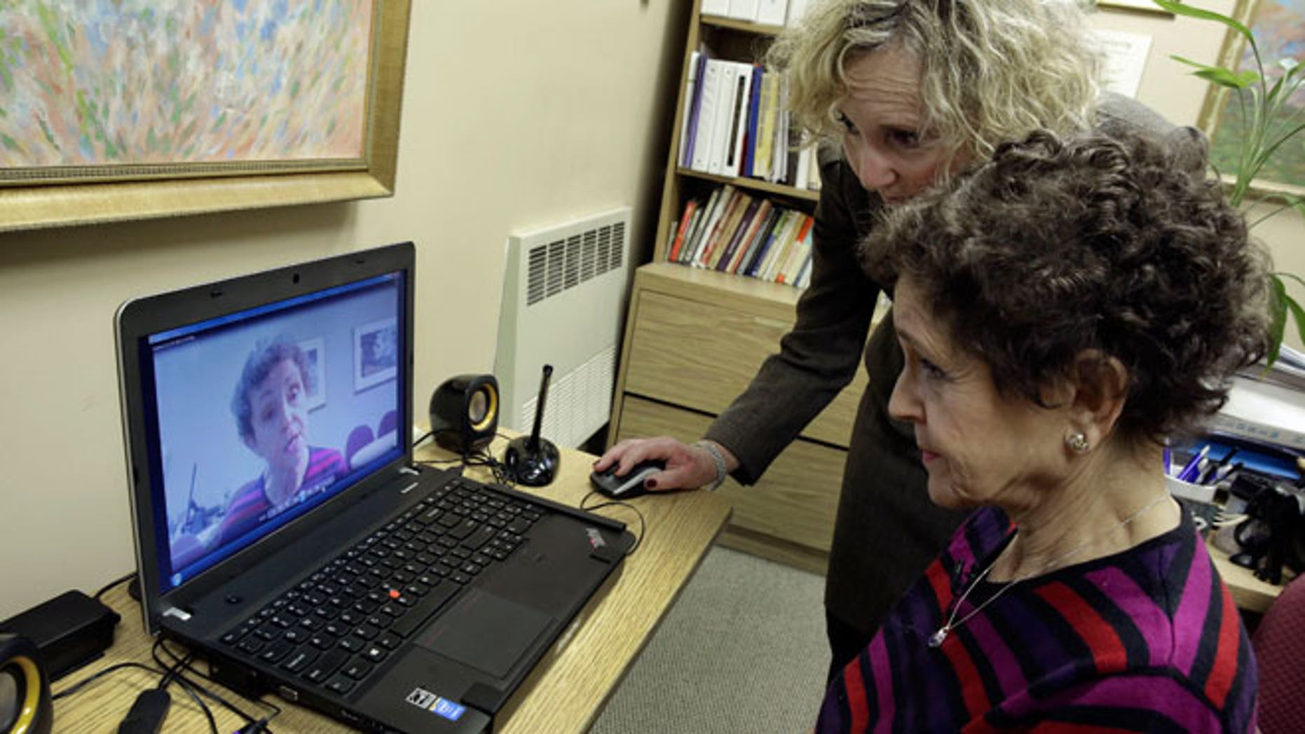 Tamara Rusoff-Hoen, right, watches a video she recorded for her mother, Louise Irving, with Charlotte Dell, Director of Social Services at The Hebrew Home of Riverdale, in New York, Wednesday, March 25, 2015. The nursing home in the Bronx has started a pilot program in which relatives record video messages for patients of Alzheimer's and other forms of dementia. The videos are played for them each morning to calm their agitation and reassure them about their surroundings and their routines.