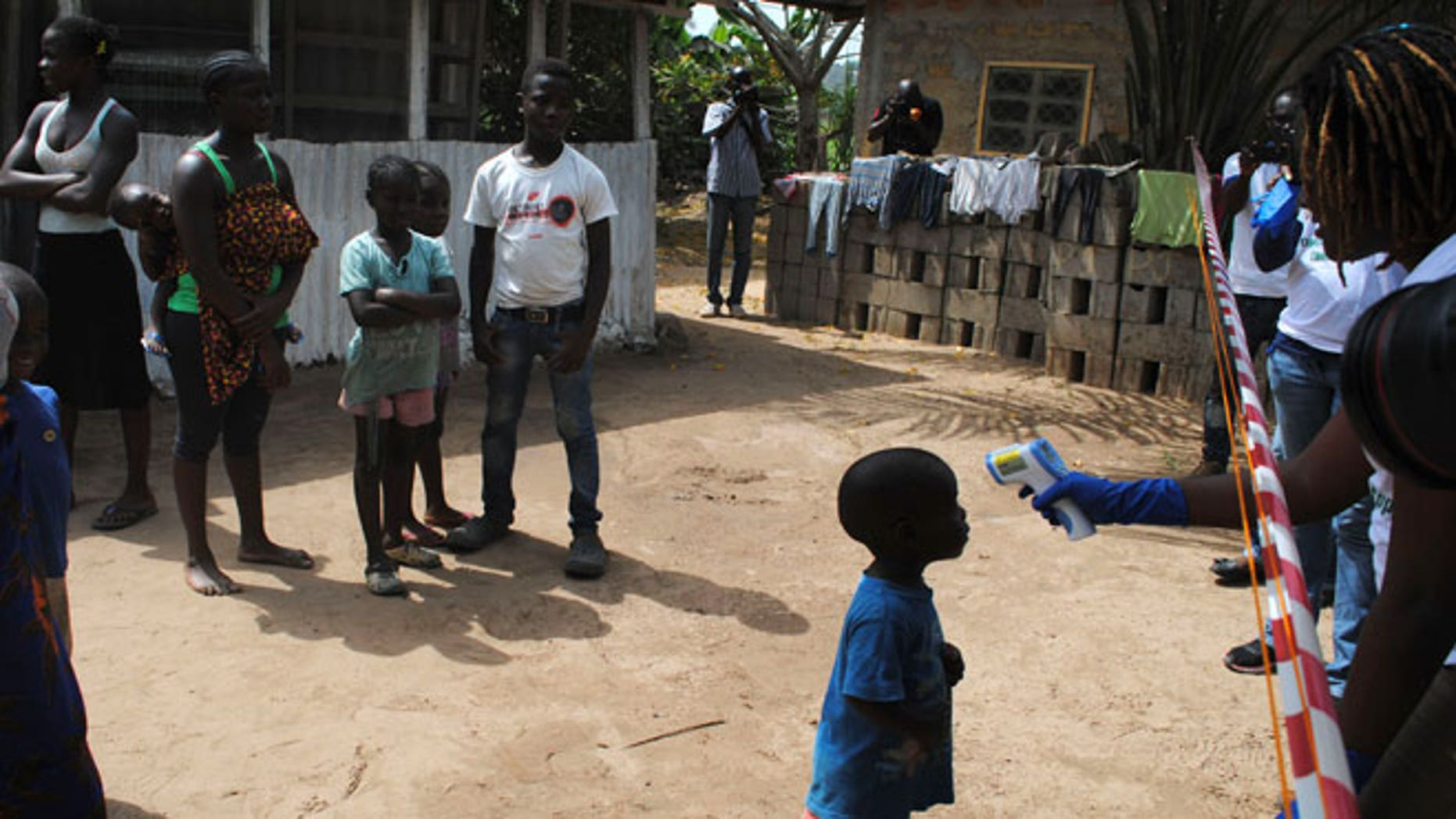 Health workers take the temperature of a boy who came in contact with a woman who died of Ebola virus in the Paynesville neighborhood of Monrovia, Liberia, January 21, 2015.