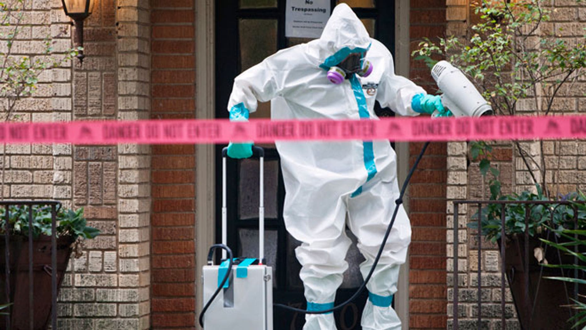 A member of the CG Environmental HazMat team disinfects the entrance to the residence of the first health worker at the Texas Health Presbyterian Hospital to contract Ebola in Dallas, Texas, October 12, 2014.